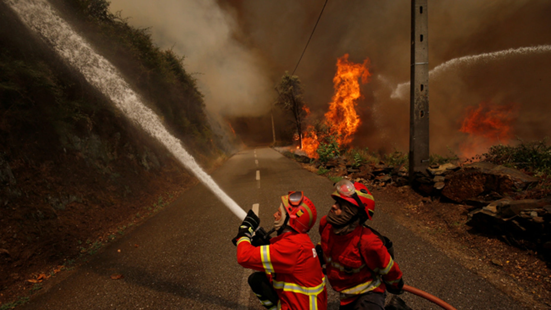 Firefighters work to put out a forest fire in the village of Sandinha, near Gois, Portugal, June 20, 2017. REUTERS/Rafael Marchante - RTS17VXR