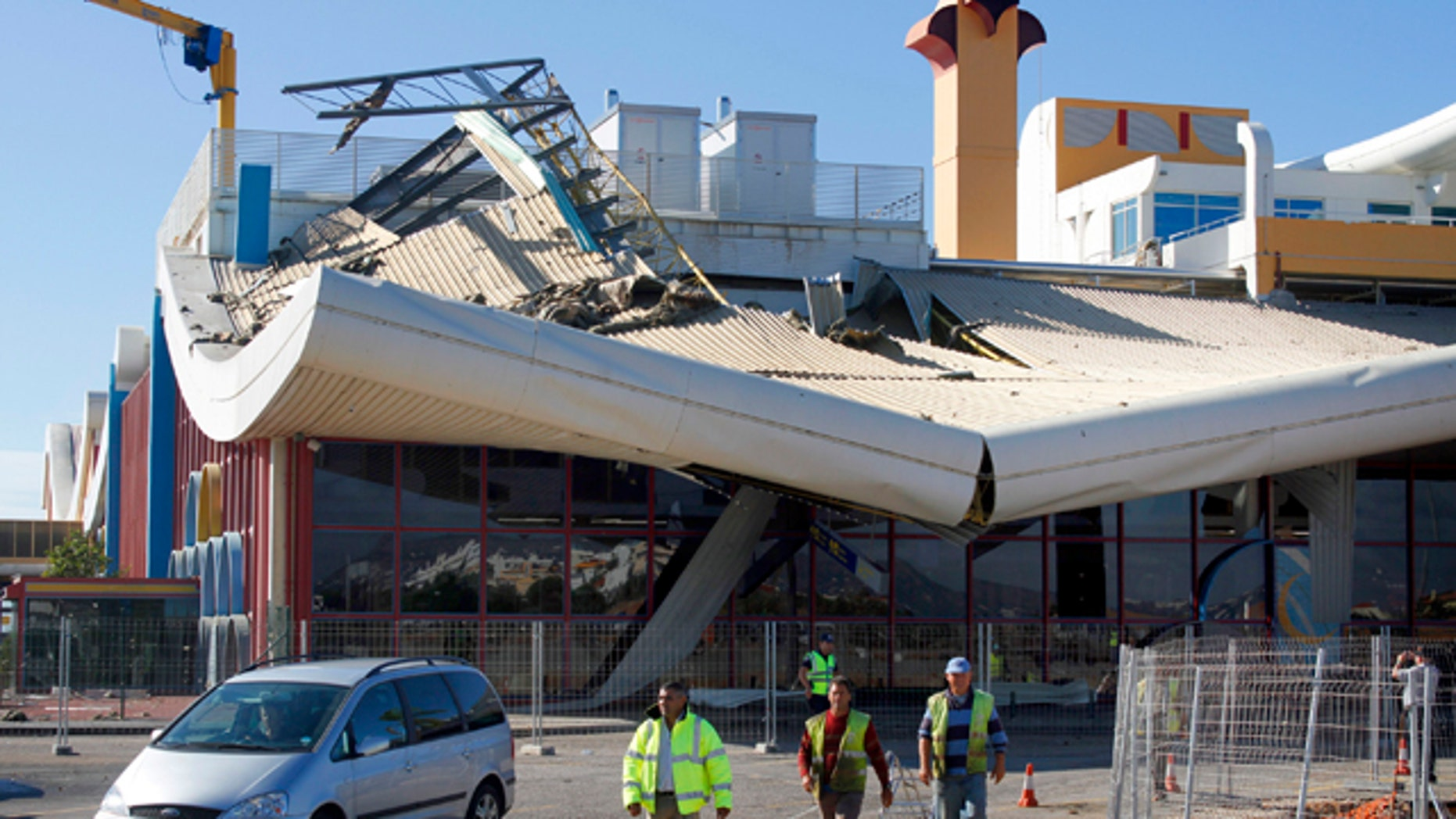 Oct. 24, 2011: Workers walk in front of the damaged building of Faro airport.