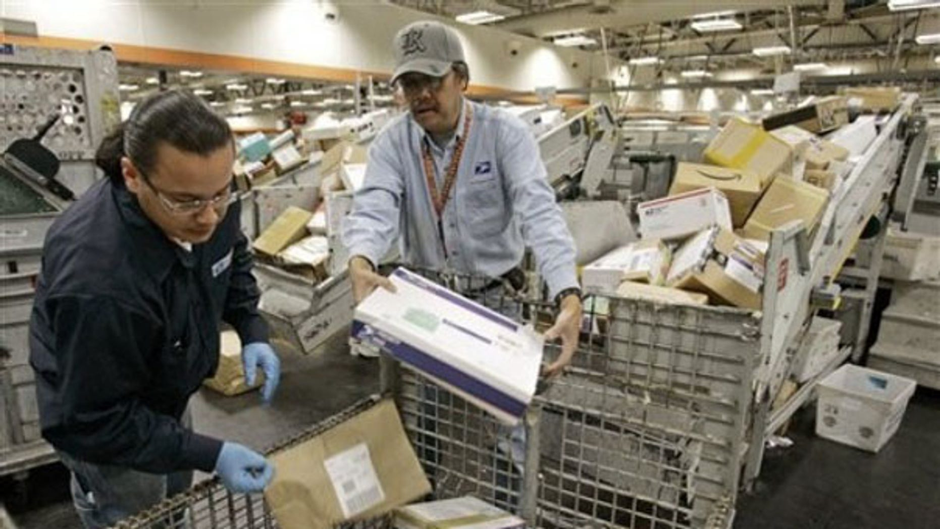 FILE: U.S. Postal Service mail handlers sort packages at the USPS San Francisco center.