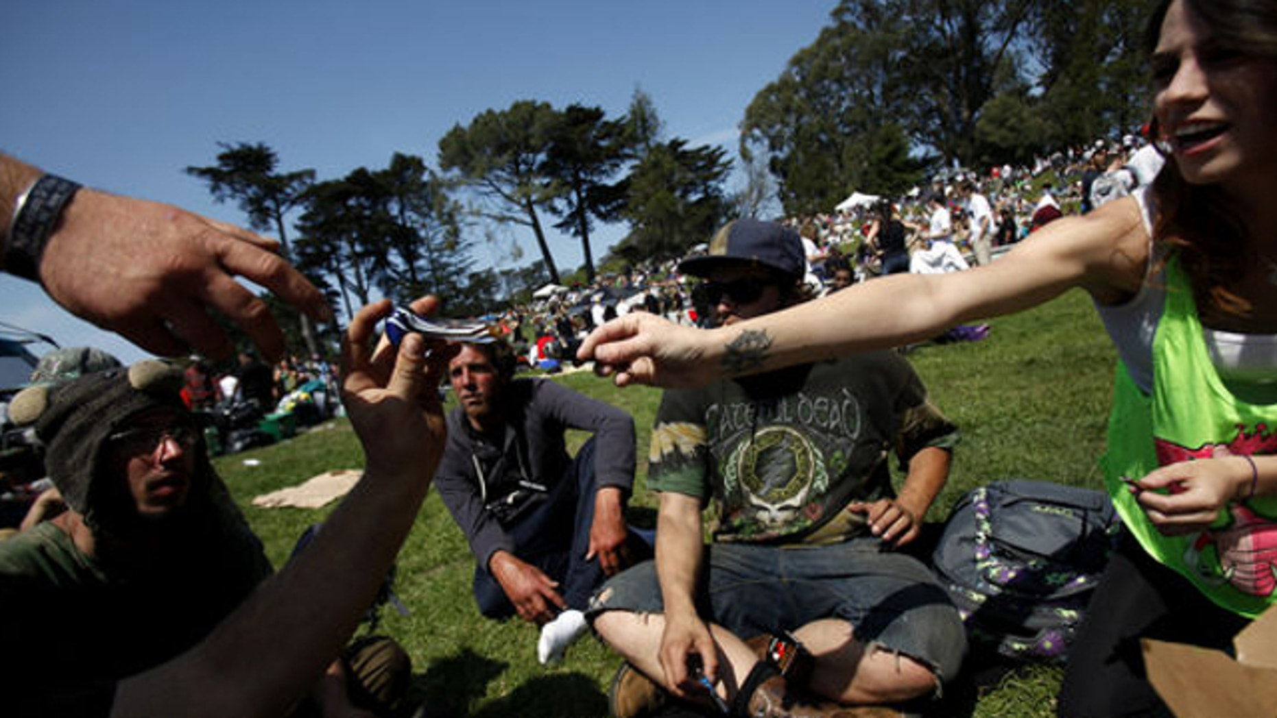 April 20, 2014: Jessica Morales, far right, passes a pipe to Brian Strelow, hand at left, during 420 celebrations at Hippie Hill in Golden Gate Park in San Francisco, Calif.