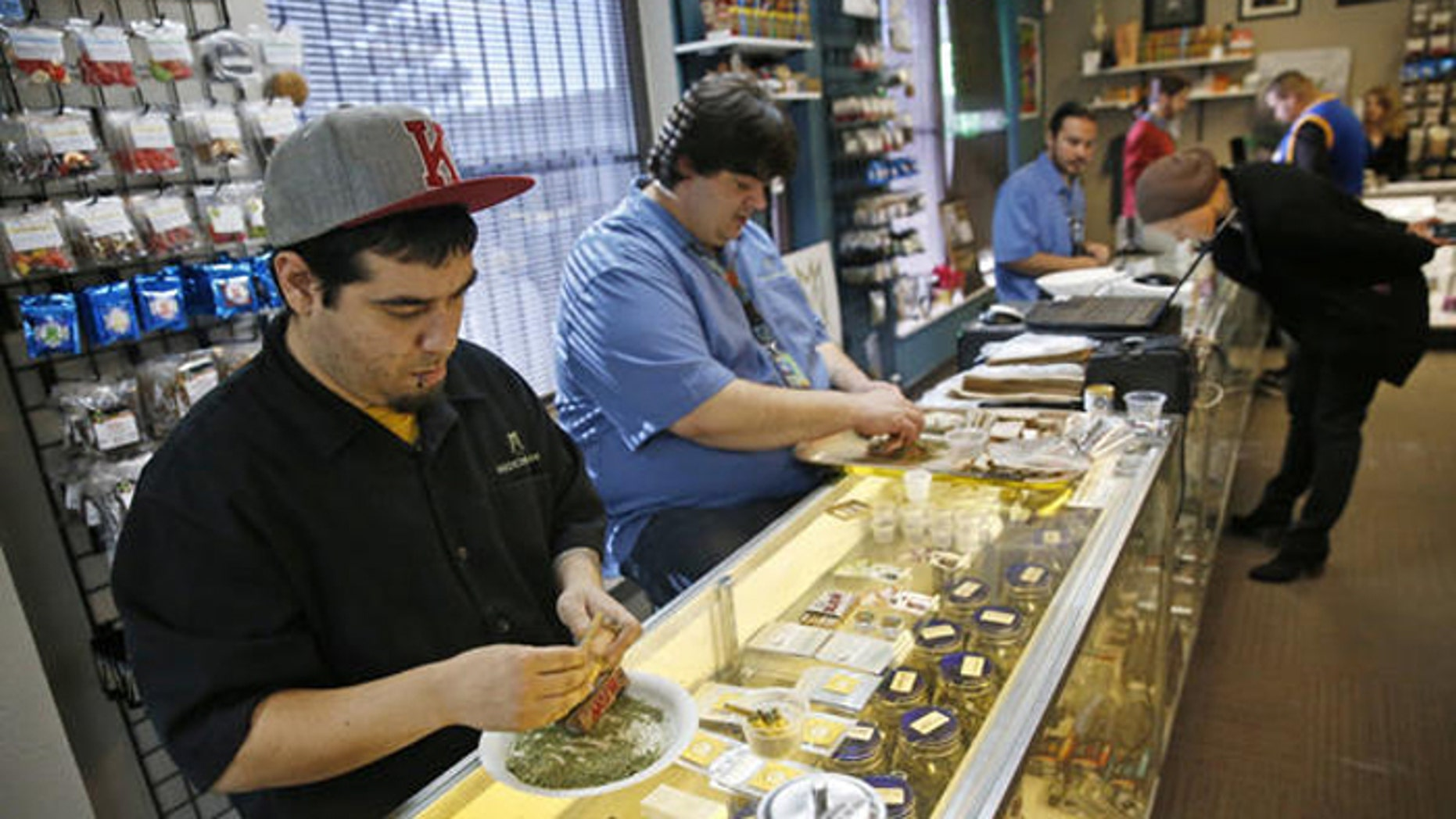 Employees roll joints behind the sales counter at Medicine Man marijuana dispensary in Denver. (AP)