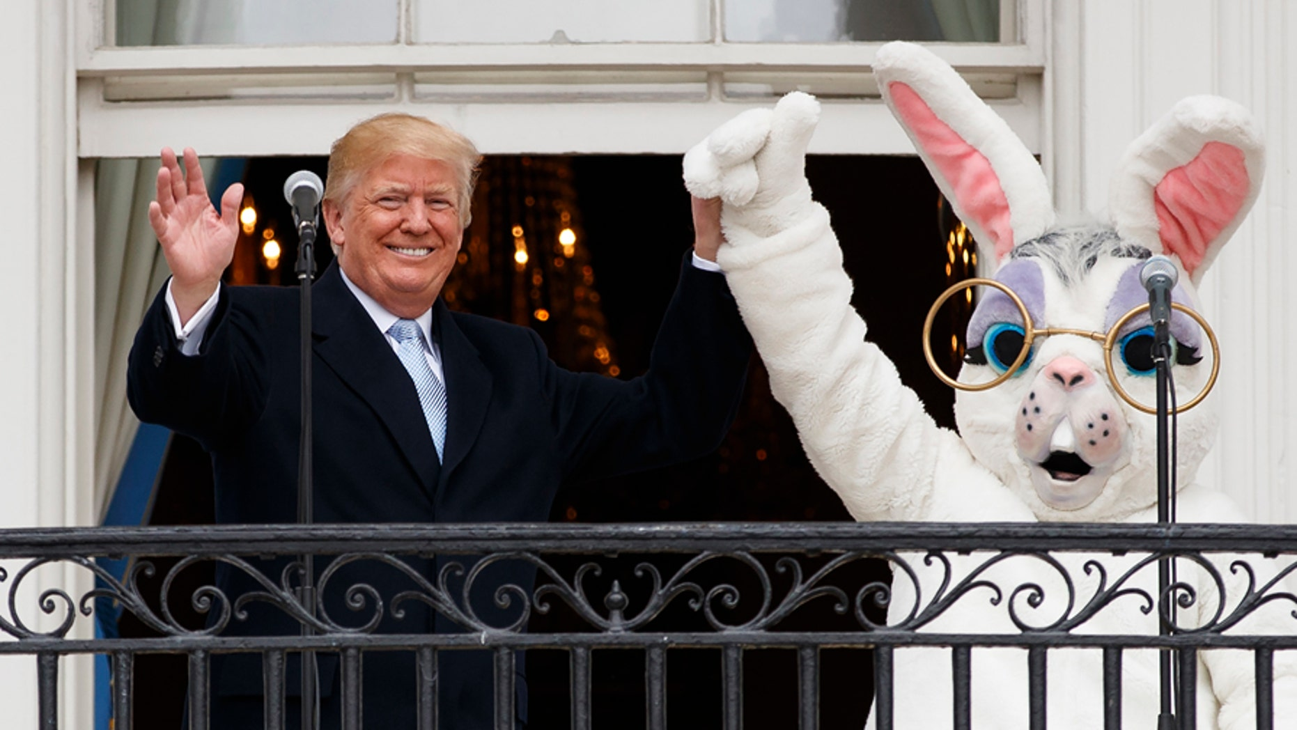 President Donald Trump holds hands with the Easter Bunny on the Truman Balcony of the White House in Washington, Monday, April 2, 2018, during the annual White House Easter Egg Roll. (AP Photo/Carolyn Kaster)