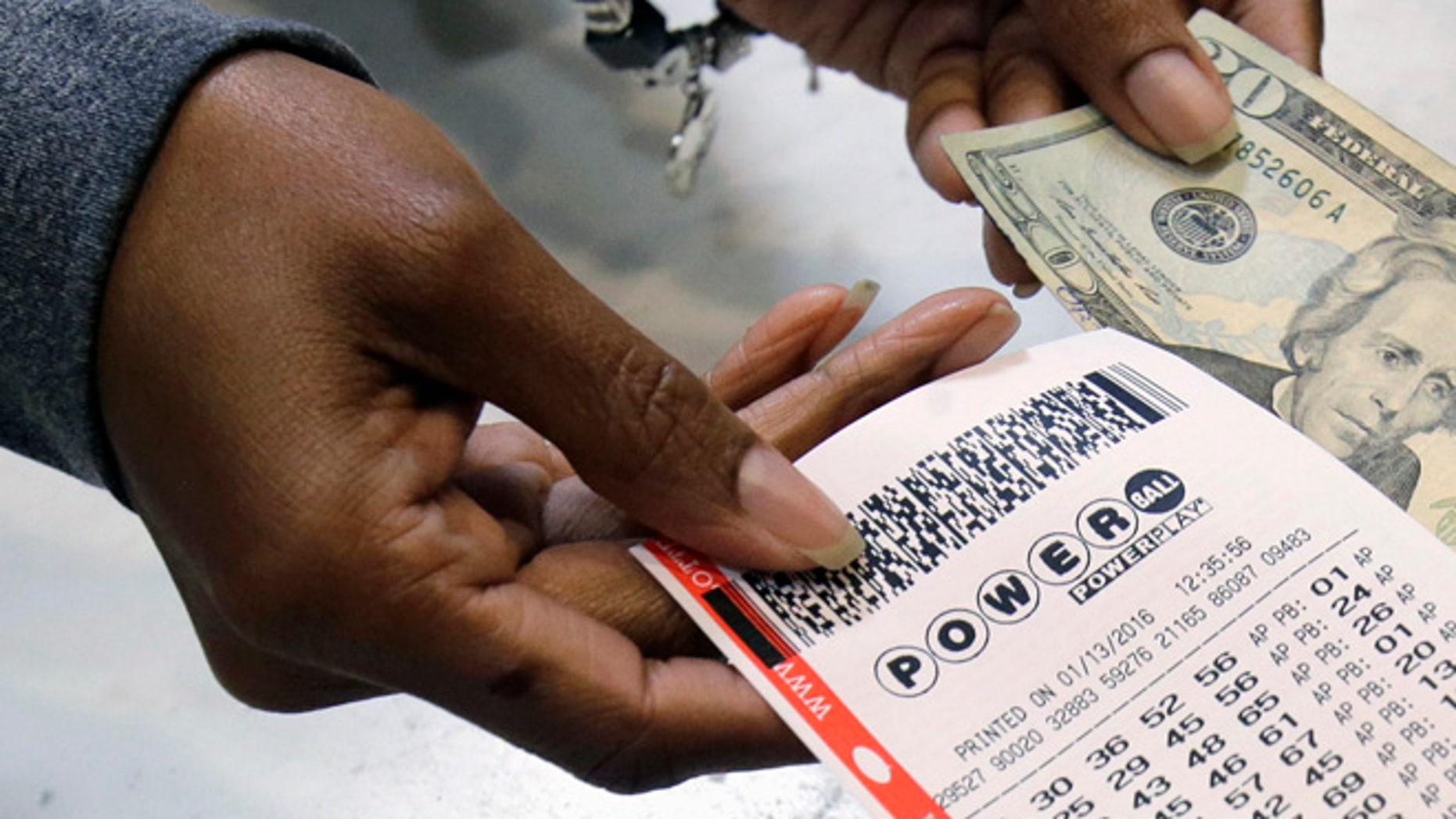 In this Jan. 13, 2016 file photo, a clerk hands over a Powerball ticket for cash at Tower City Lottery Stop in Cleveland. Powerball estimates that its jackpot for the May 4, 2016