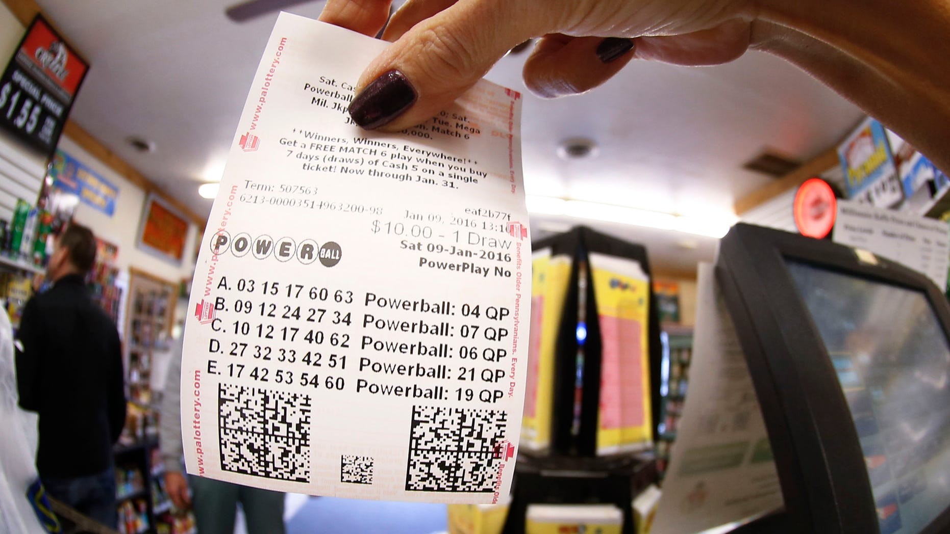 In this photo made with a fisheye lens a clerk hands a patron his $10 worth of chances for the upcoming Powerball drawing on Saturday, Jan. 9, 2016, in Cranberry Township, Pa. The Powerball jackpot has reached a record $900 million, with the drawing Saturday night. (AP Photo/Keith Srakocic)