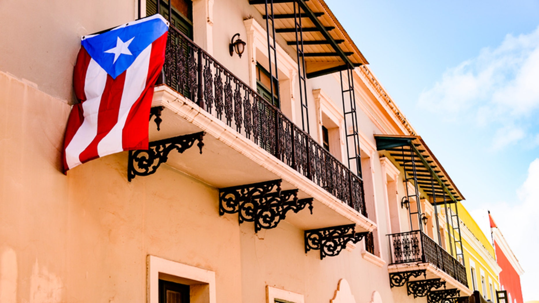 Colorful house  facades along a street in Old San Juan, Puerto Rico with a Puerto Rican flag hanging down from one of the balconies