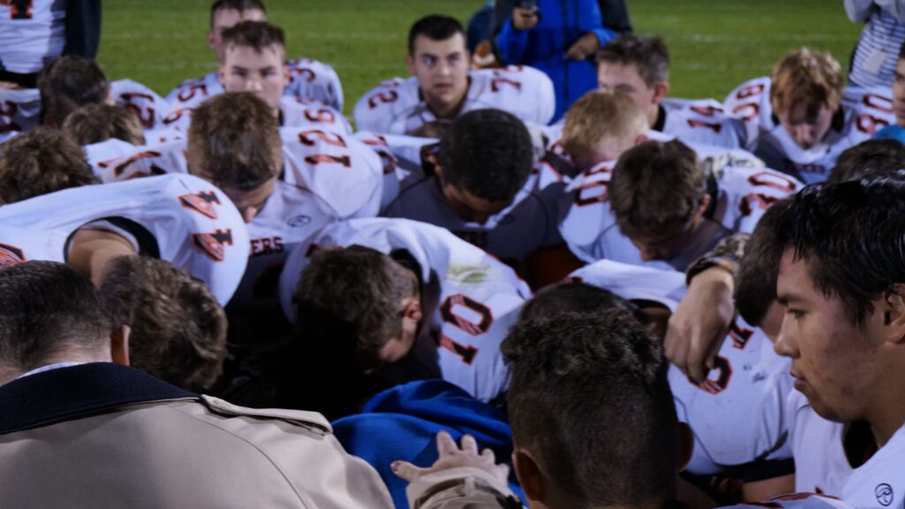 October 16: Coach Kennedy prays on the field after the high school's homecoming game. (Courtesy Liberty Institute)