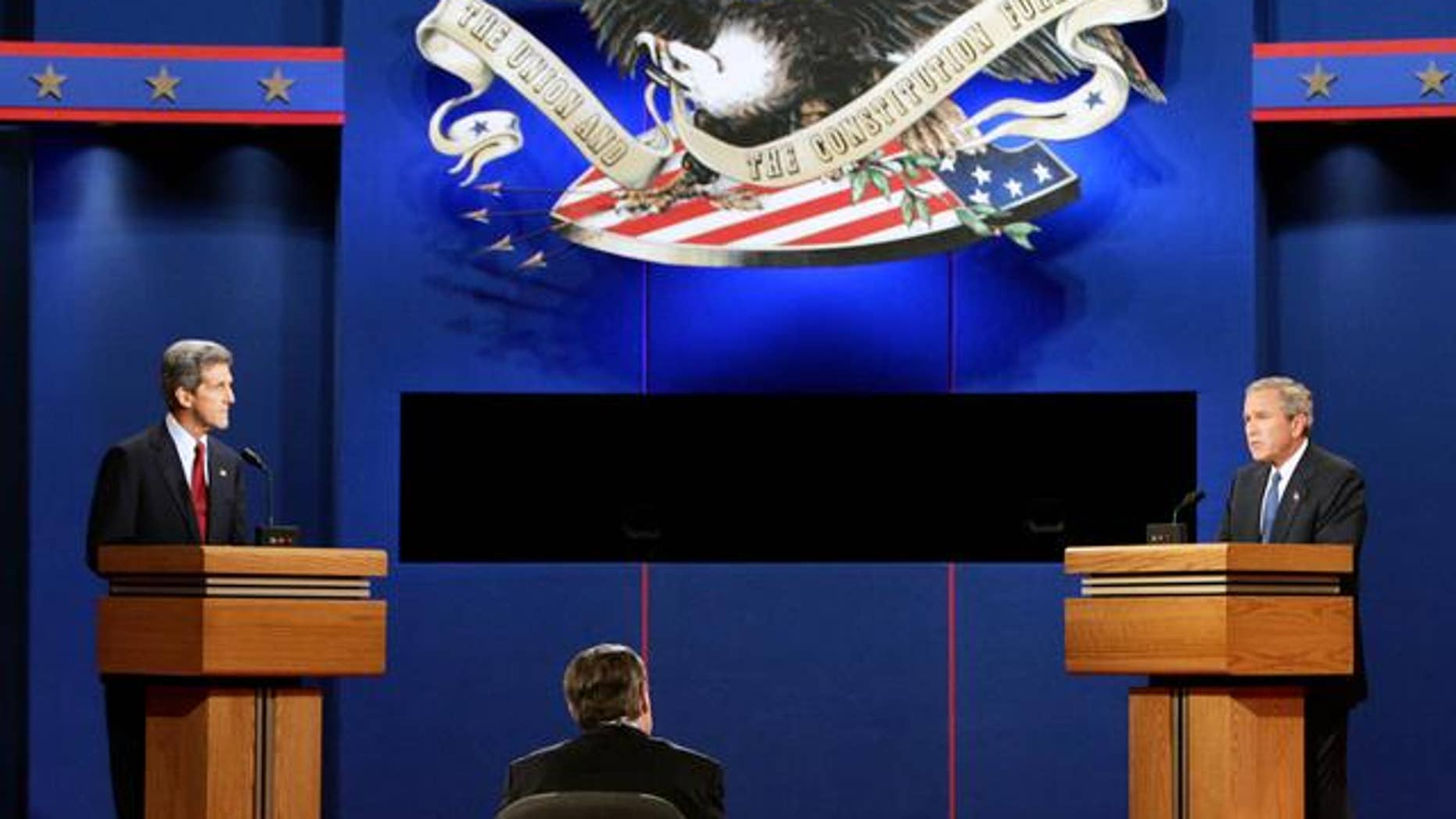 Democratic presidential candidate John Kerry, left,  listens to President Bush during the presidential debate in Coral Gables, Fla., Thursday, Sept. 30 2004. Debate moderator Jim Lehrer is at center.  (AP Photo/Ron Edmonds)