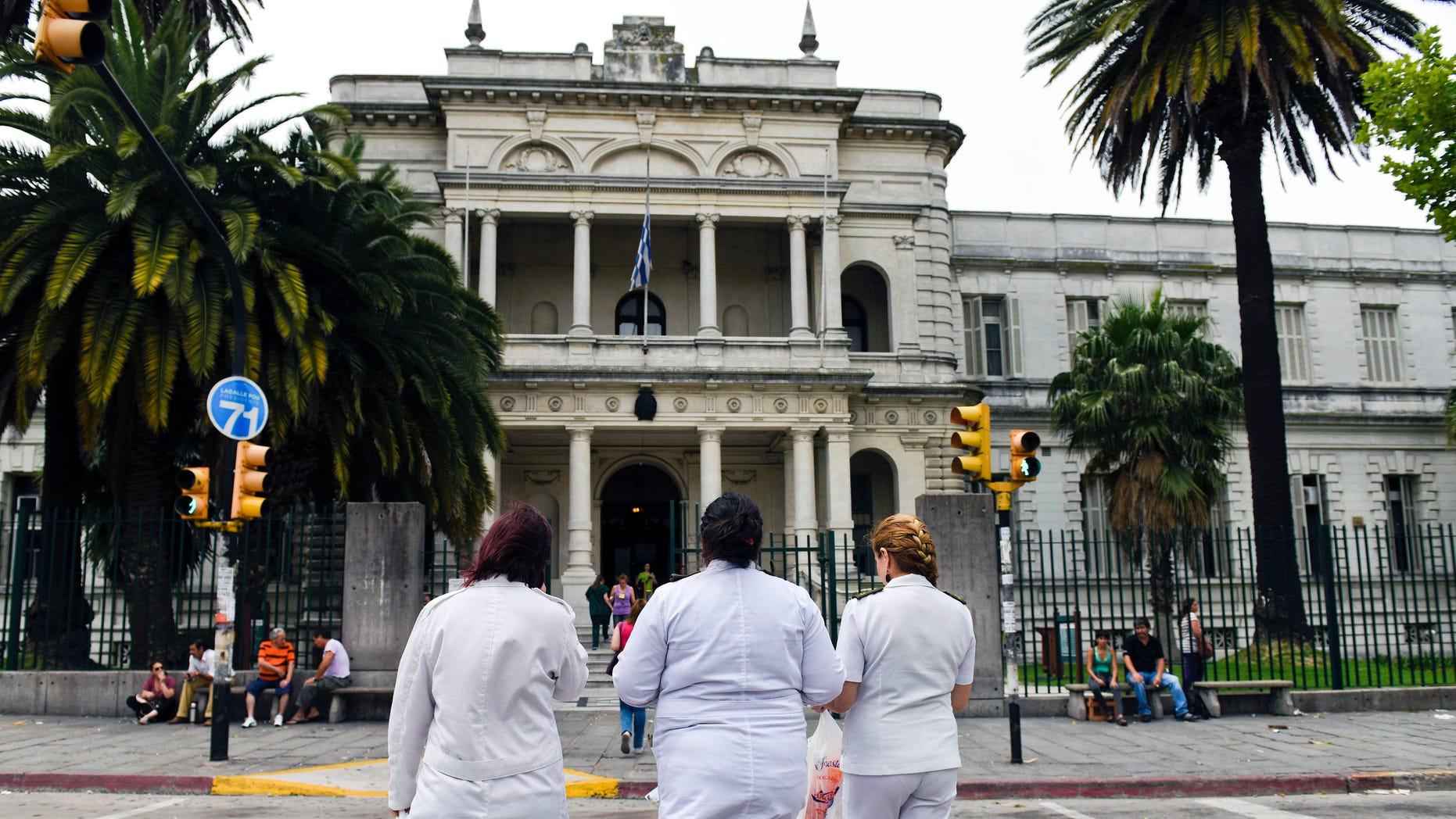 Three doctors enter the military hospital in Montevideo, Uruguay, Sunday, Dec. 7, 2014.