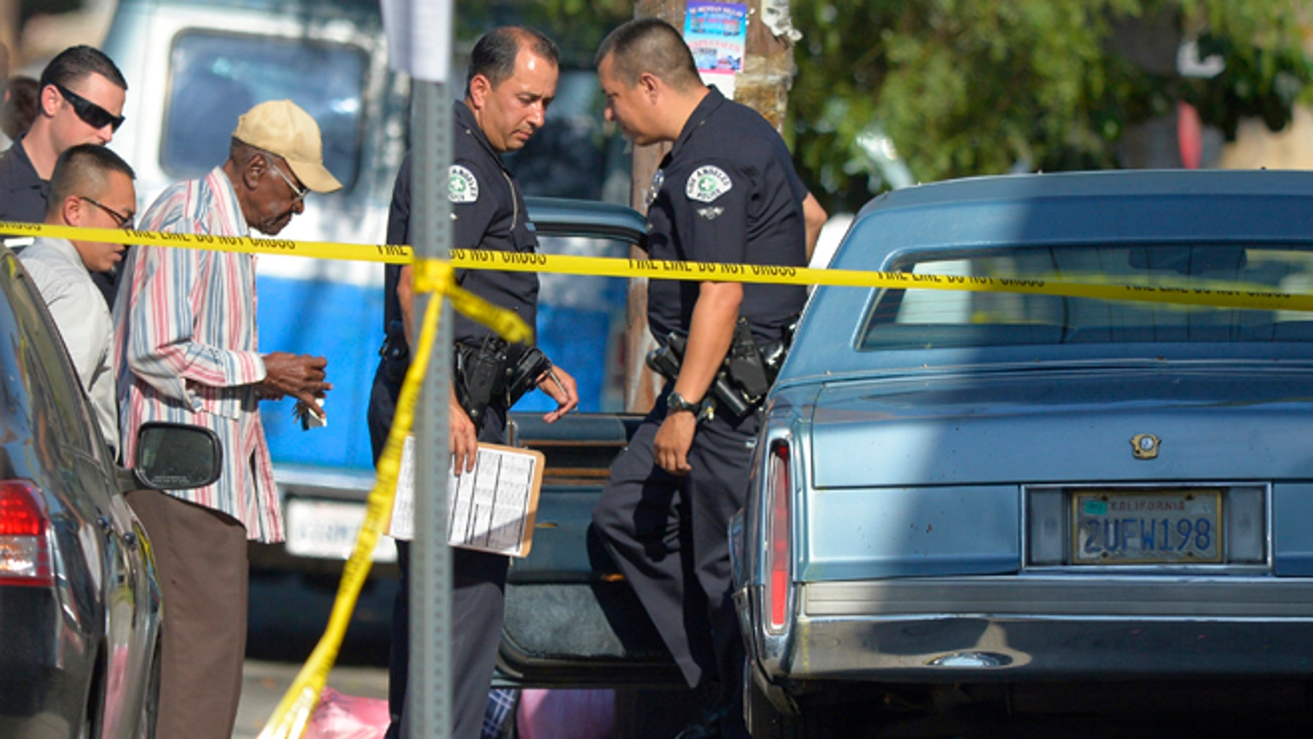 August 29, 2012: Preston Carter, left, 100, talks with police officers after police say his car went onto a sidewalk and plowed into a group of parents and children outside a South Los Angeles elementary school in Los Angeles. Nine children and two adults were injured in the wreck.