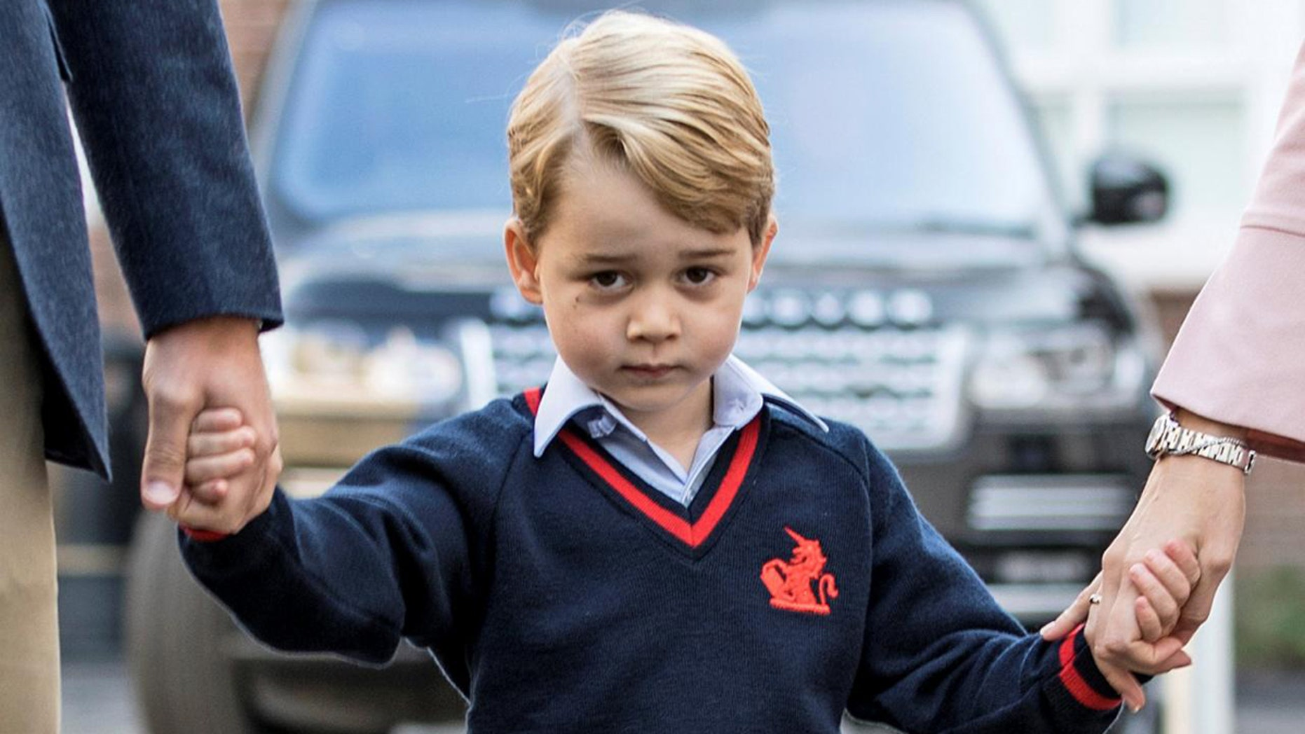 Prince George is seen holding his parents hands outside Kensington Palance in the United Kingdom.