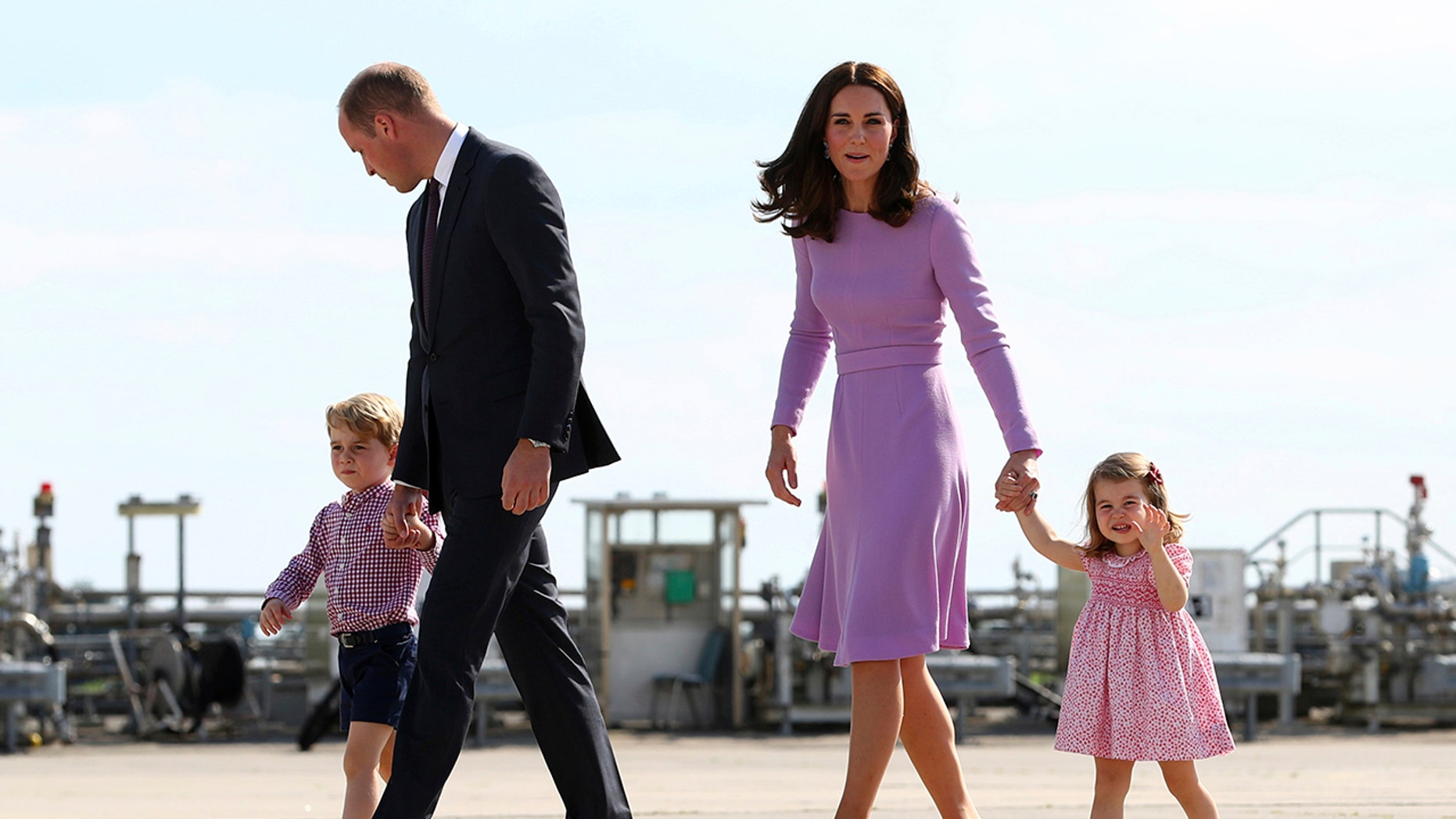 In this Friday, July 21, 2017 file photo Britain's Prince William, second left, and his wife Kate, the Duchess of Cambridge, second right, and their children, Prince George, left, and Princess Charlotte, right are on their way to board a plane in Hamburg, Germany