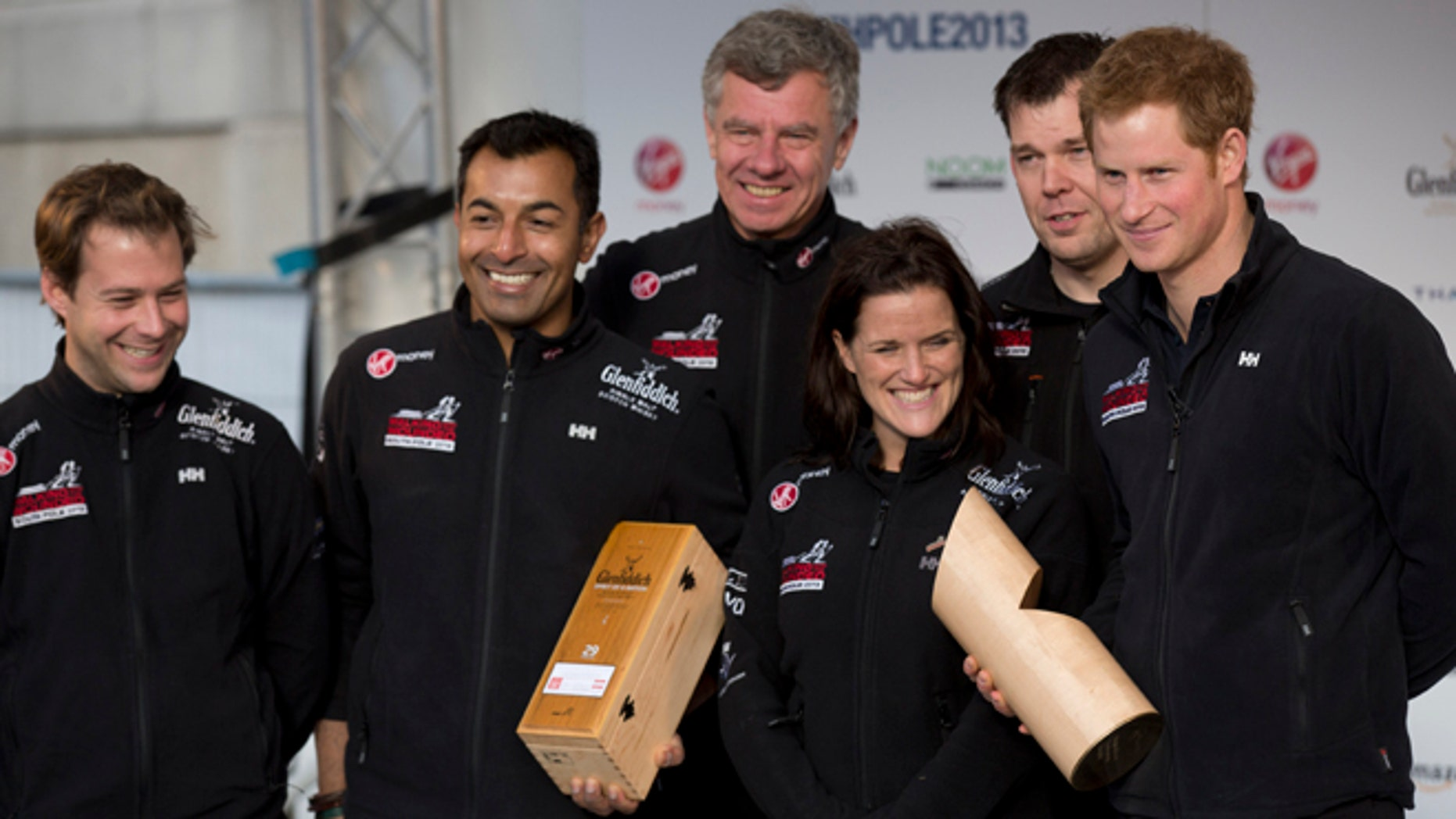 """Nov. 14, 2013: Britain's Prince Harry, right, poses for a group photograph on stage with his teammates, from left, single leg amputee Guy Disney, single leg amputee Ibrar Ali MC, team mentor Richard Eyre, single leg amputee Kate Philp and double leg amputee Duncan Slater during the """"Walking With The Wounded South Pole Allied Challenge"""" departure event in Trafalgar Square, London."""