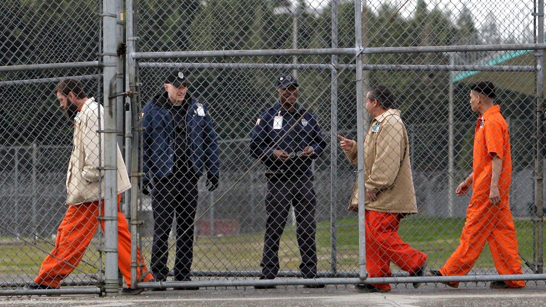 FILE - In this Feb. 17, 2011 file photo, inmates walk past correctional officers at the Washington Corrections Center in Shelton, Wash. Gov. Jay Inslee said Tuesday, Dec. 22, 2015 that more than 3,000 prisoners in Washington have been mistakenly released early since 2002 because of an error by the state's Department of Corrections. (AP Photo/Elaine Thompson, file)