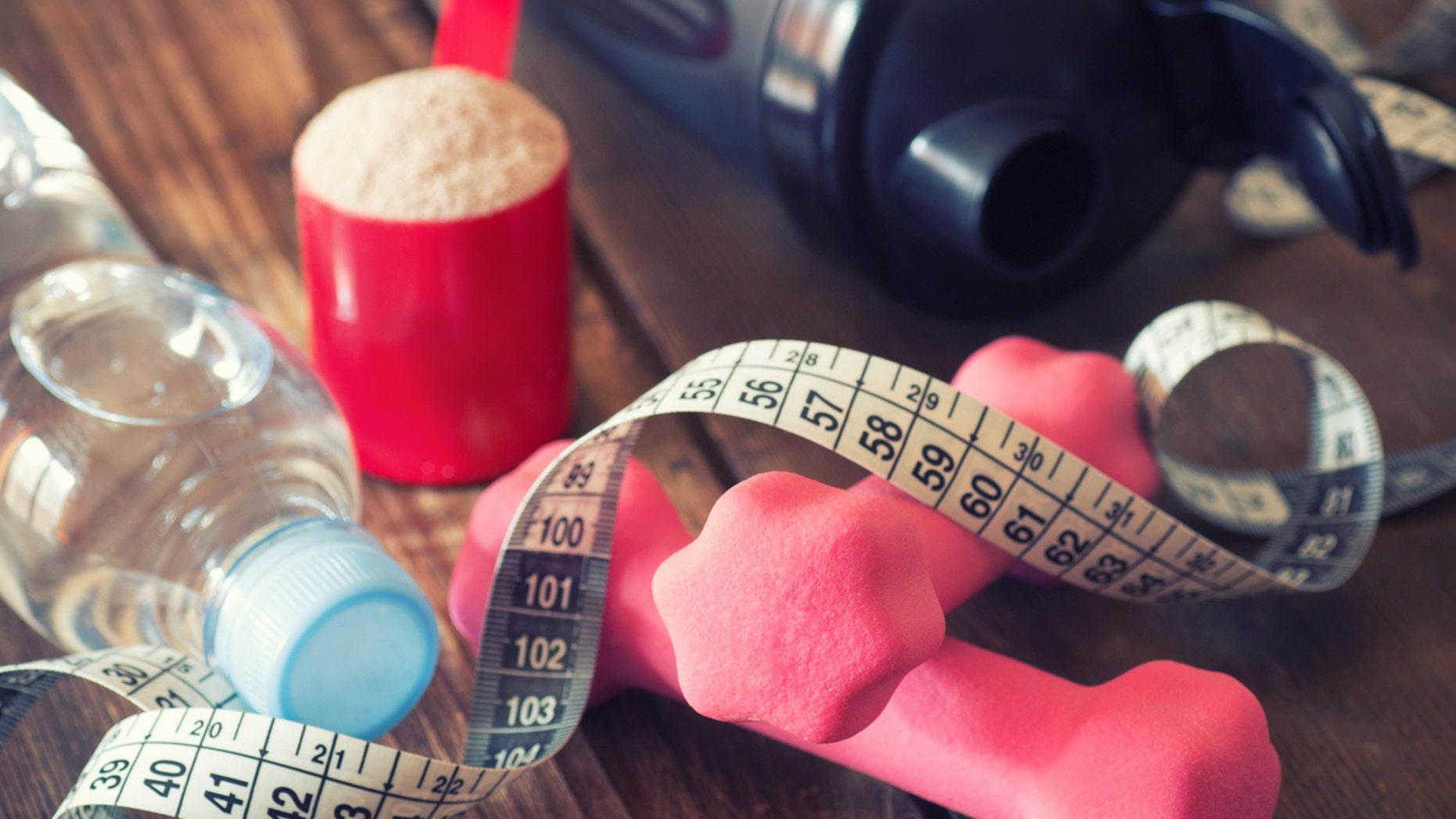 weight loss concept with tape measure whey powder, pink dumbbells and black shaker