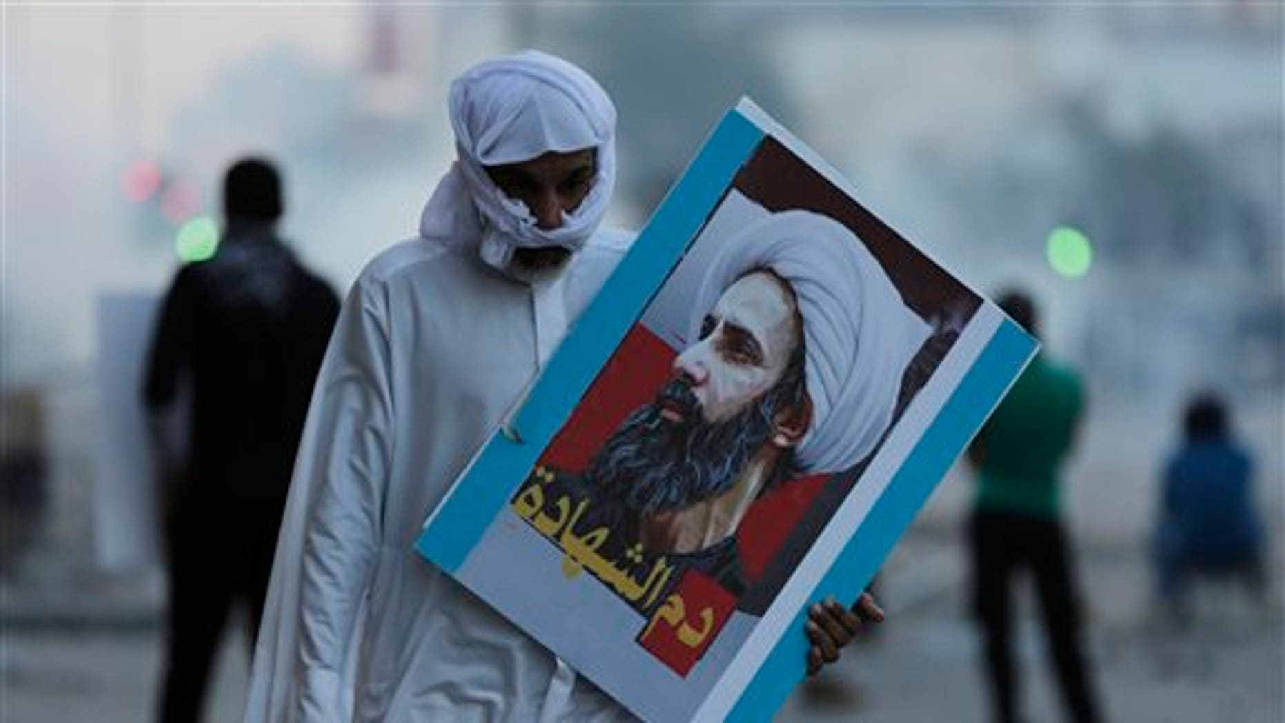"""A Bahraini protester carries a picture of Saudi Shiite cleric Sheikh Nimr al-Nimr that reads, """"blood of the martyr,"""" during clashes with riot police in Sitra, Bahrain, Friday, Jan. 8, 2016. (AP Photo/Hasan Jamali)"""