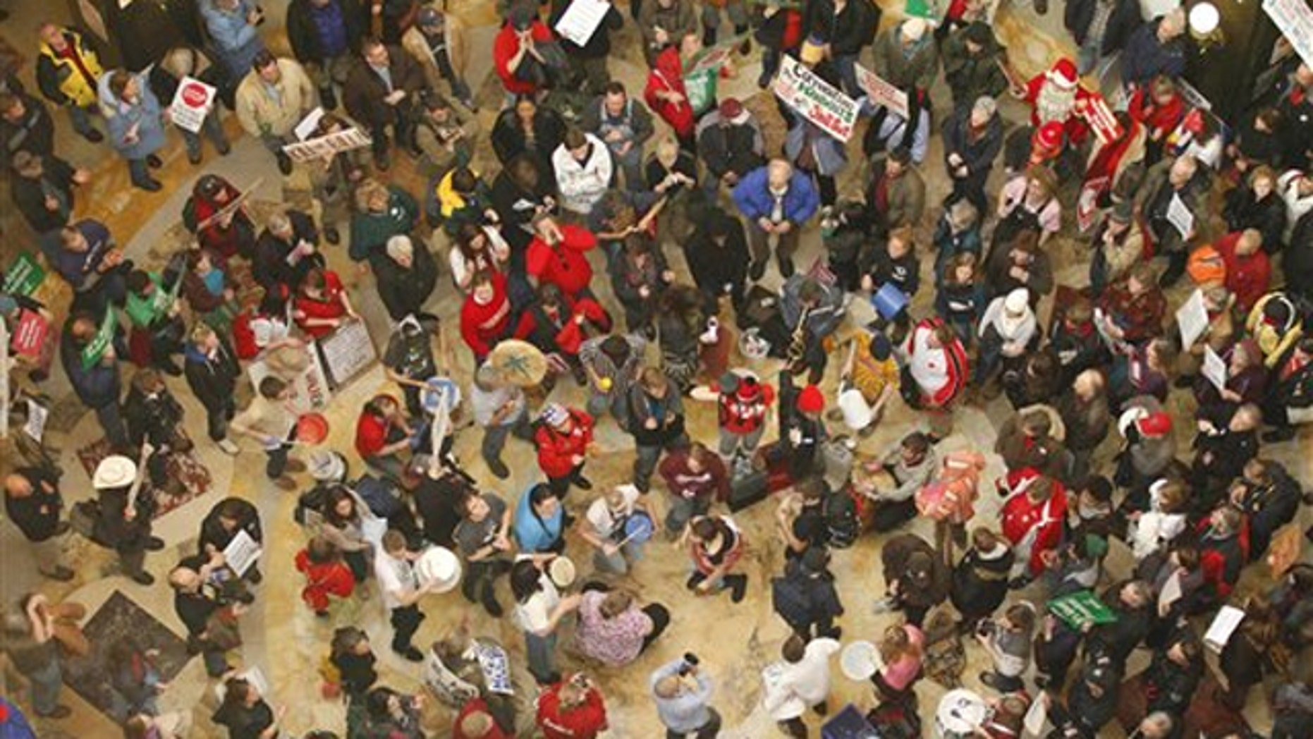Protesters bang drums and chant inside the state Capitol Feb. 22 in Madison, Wis.
