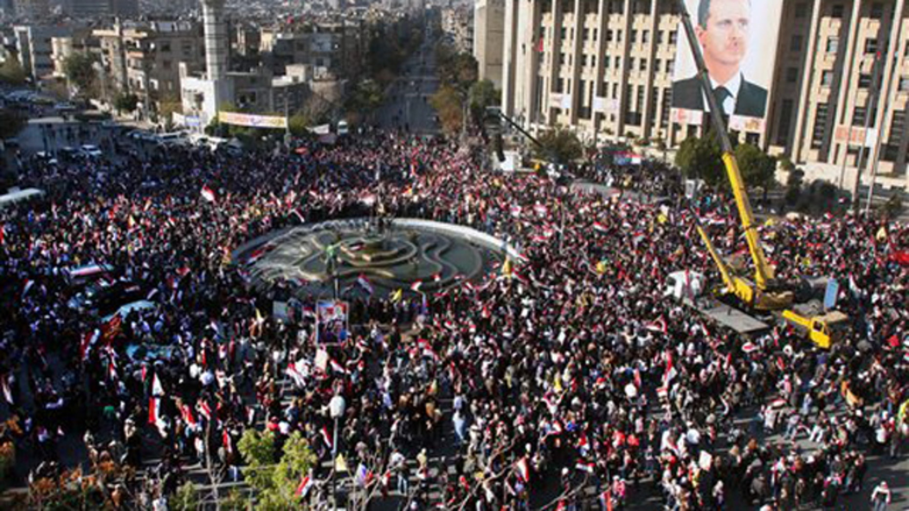 Pro-Syrian regime protesters gather during a protest against sanctions, in Damascus, Syria, on Friday Dec. 2, 2011.