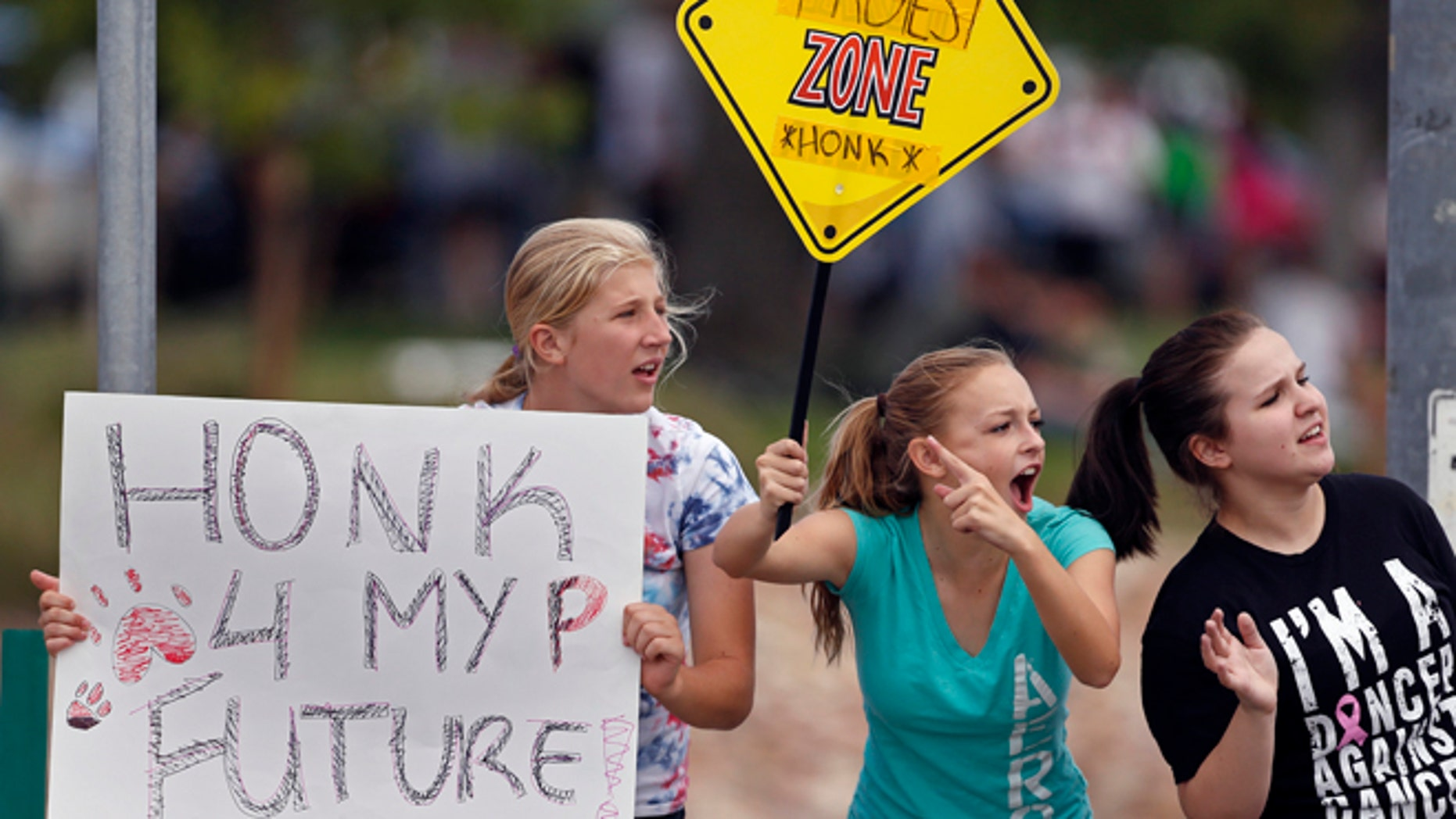 Sept. 23, 2014: Protesting Pamona High School students, left to right, Ciana Vrtikapa, Tori Suyak, and Becca Ferris engage with passing motorists in a busy intersection near their school, during a multi-school protest against a Jefferson County School Board proposal to emphasize patriotism and downplay civil unrest in the teaching of U.S. history, in Arvada, Colo. (AP)