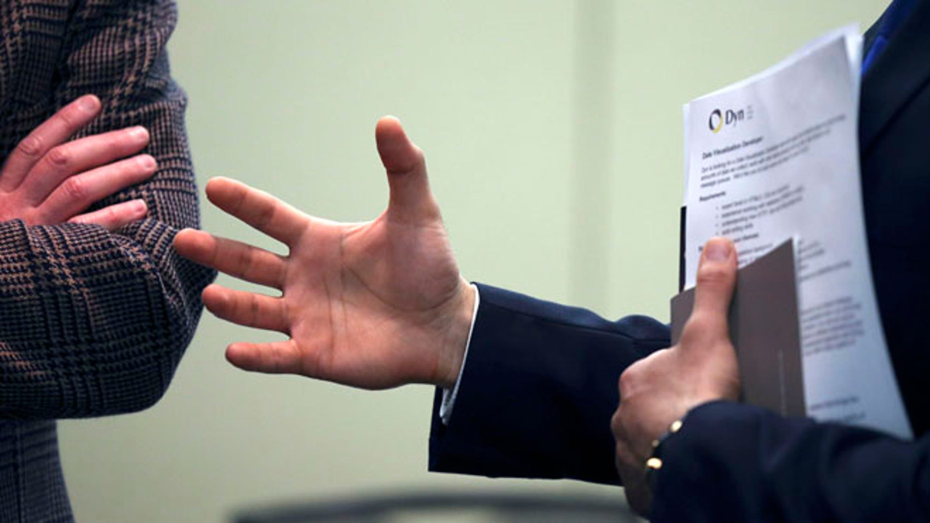 Feb. 25, 2013: A job seeker gestures while speaking to a company representative during a job fair in Boston.