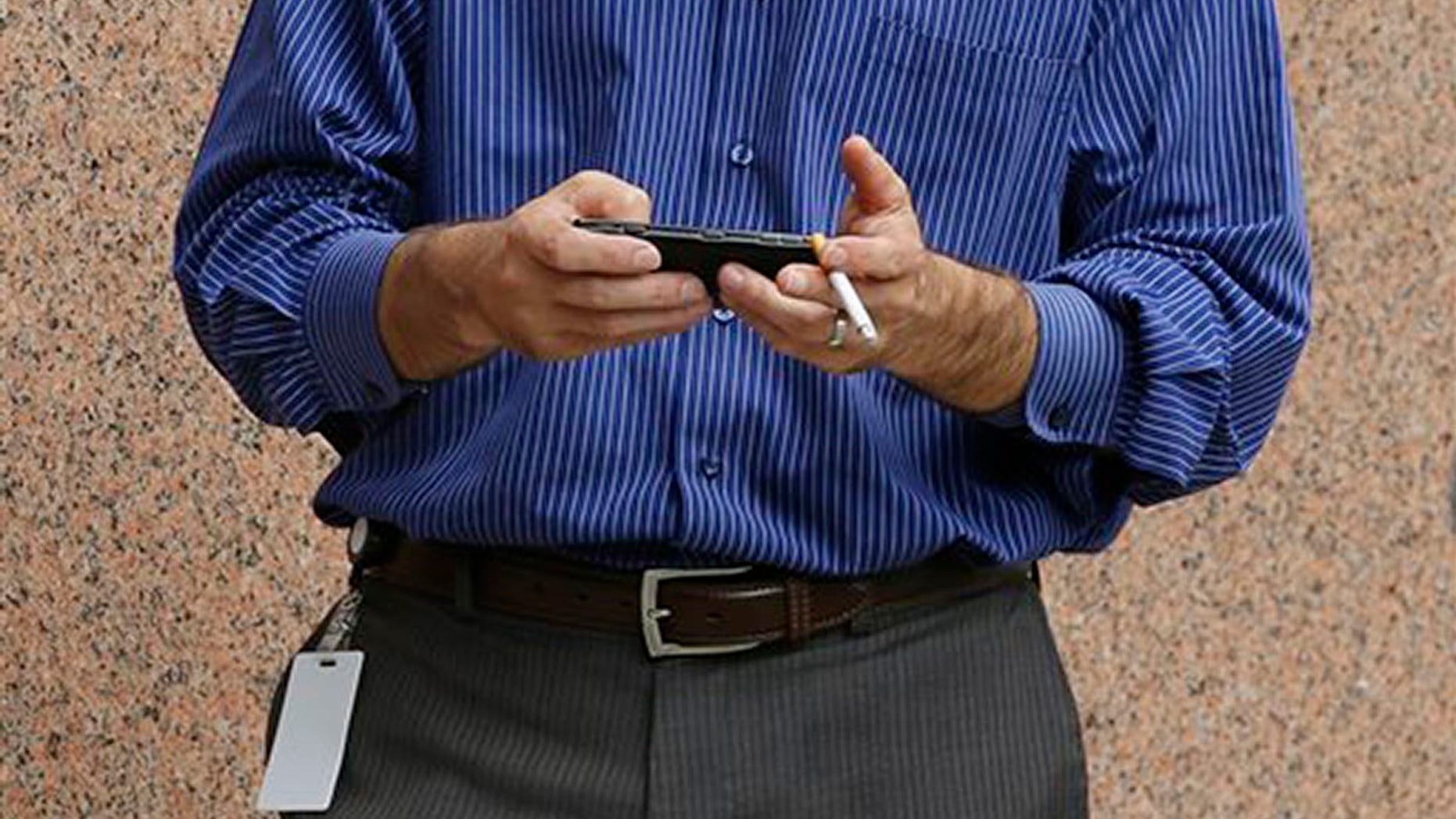 A man checks his cell phone while smoking outside an office building, Tuesday, July 21, 2015, in Providence, R.I. Providence is considering an ordinance that would prohibit smoking throughout downtown.