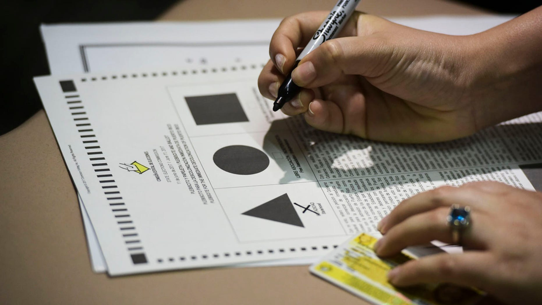 A Puerto Rican citizen votes during the fifth referendum in San Juan, Puerto Rico, Sunday, June 11, 2017. Residents of the U.S. Territory had to choose between the options of statehood, free association/independence and current territorial status. (AP Photo/Carlos Giusti)