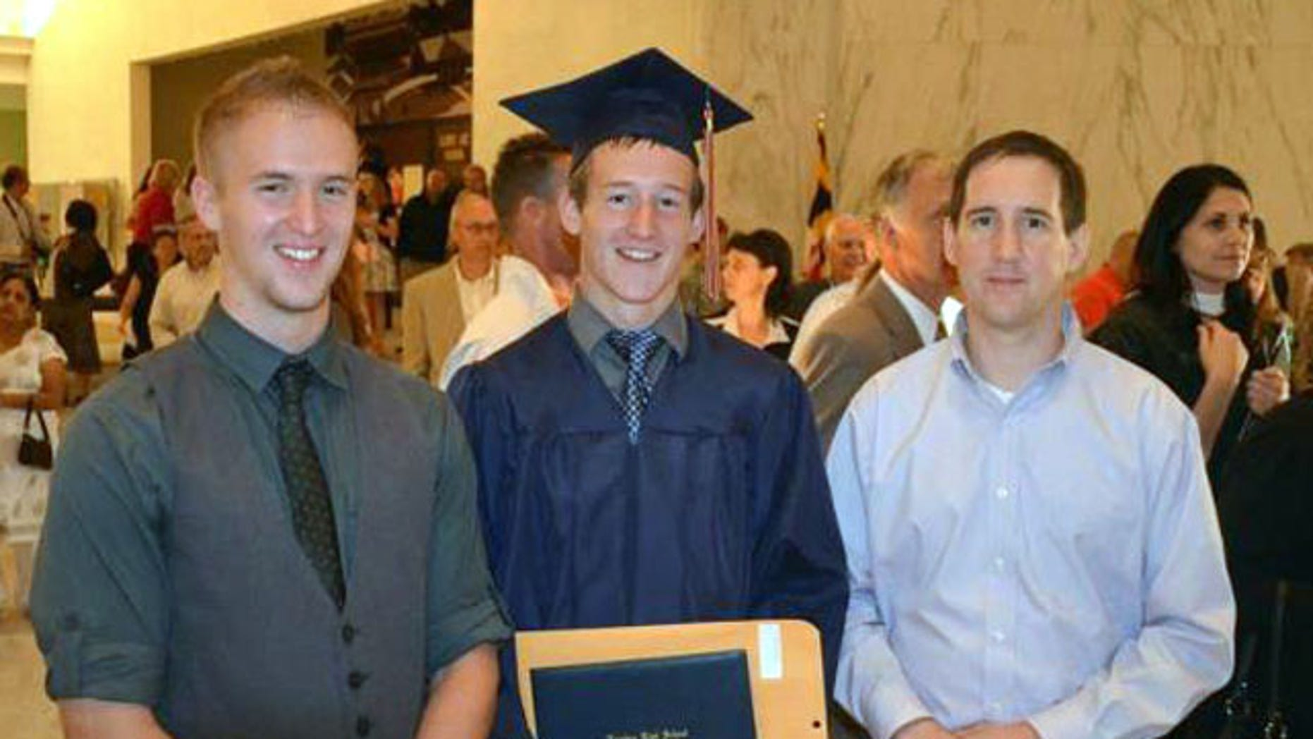 June 9, 2012: Justin Strine, left, poses with his younger brother Jamie Strine, center, and older brother, Jim Strine, at Jamies high school graduation in Hershey, PA. Justin Strine's hopes for a military career as an Army officer ended after he was kicked out from ROTC for participating in a riot at Penn State after Hall of Fame coach Joe Paterno's firing in November 2011. (AP)