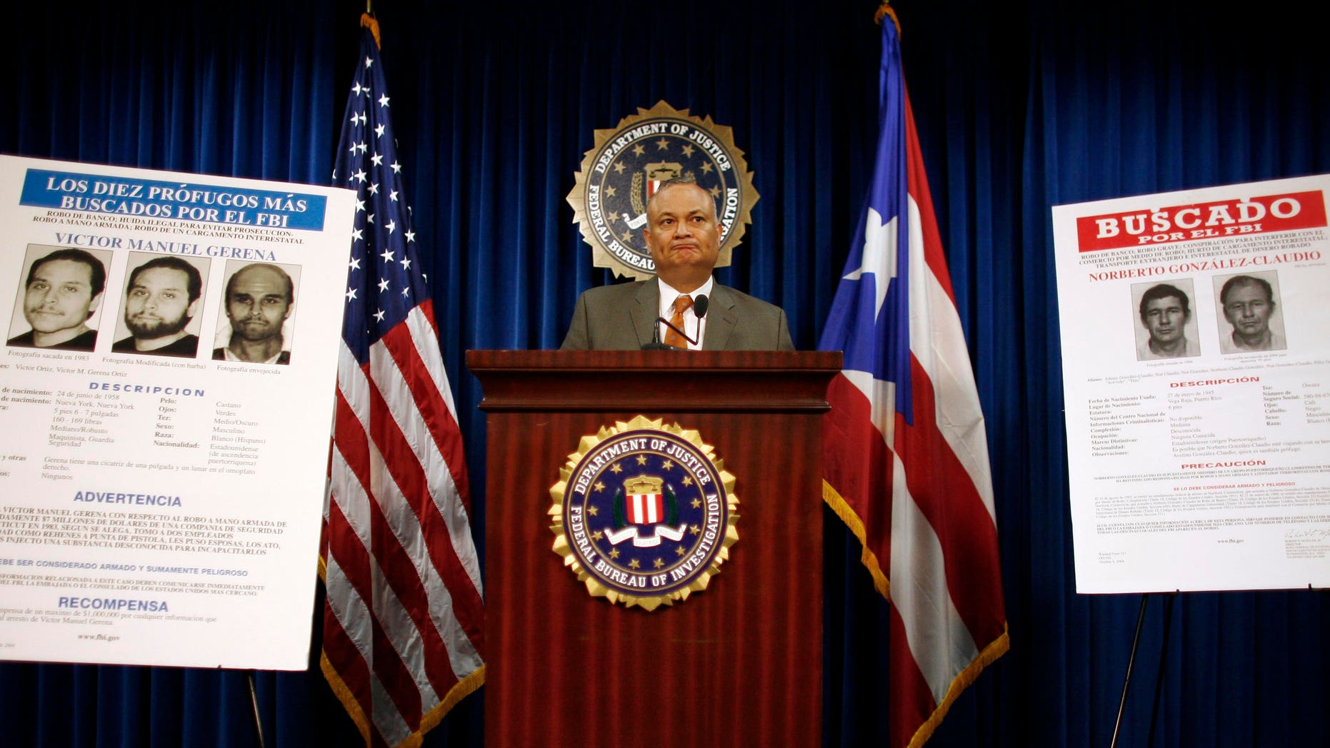 Puerto Rico's top FBI official Luis Fraticelli stands next to a wanted poster showing Norberto Gonzalez Claudio, right, at a news conference after Claudio's arrest, at FBI headquarters in San Juan, Tuesday May 10, 2011. The poster on left shows Victor Manuel Gerena who the FBI believes is living in Cuba. Claudio and Gerena are two of three alleged Puerto Rican militants sought in a 1983 Connecticut robbery that according to authorities was among the largest in U.S. history at the time. (AP Photo/Ricardo Arduengo))