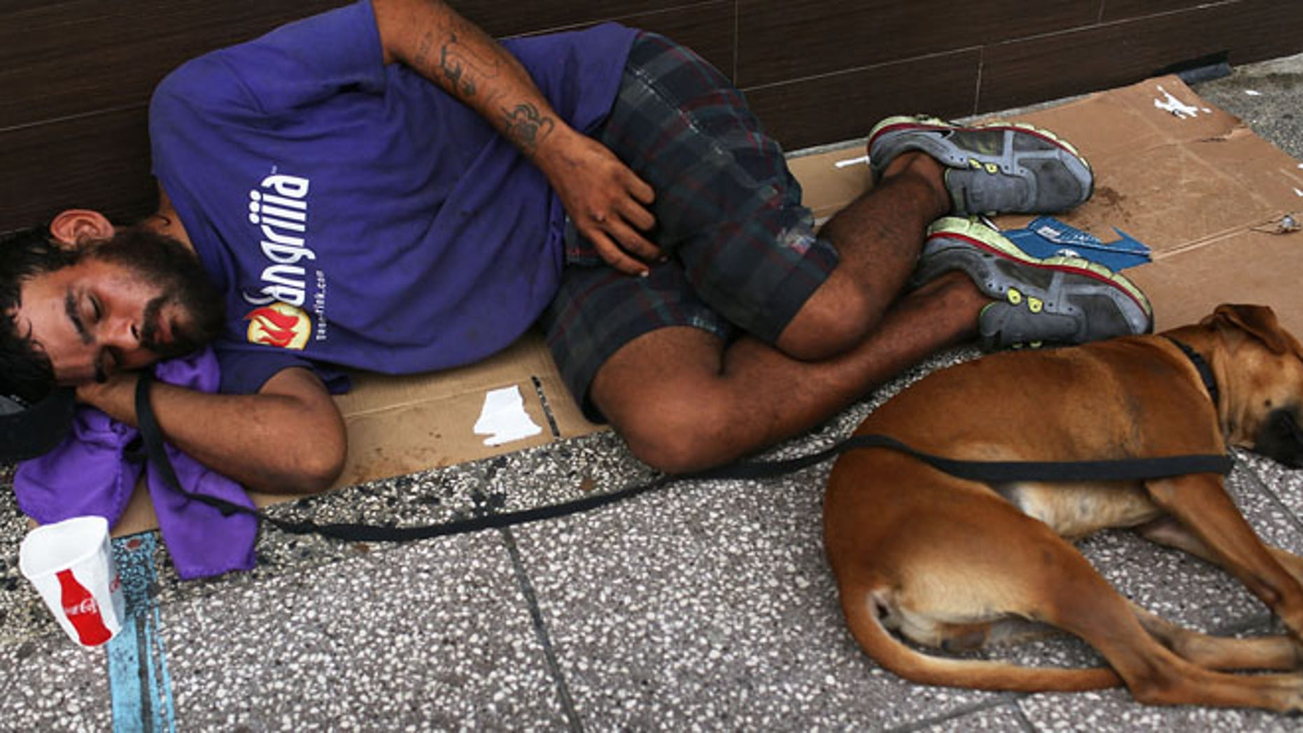 SAN JUAN, PUERTO RICO - JULY 01:  A man sleeps on the sidewalk with a dog on July 1, 2015 in San Juan, Puerto Rico. The island's residents are dealing with increasing economic hardships and a financial crisis that has resulted in the government's $72 billion debt.  Governor Alejandro  Garcia Padilla said in a speech recently  that the people will have to sacrifice and share in the responsibilities for pulling the island out of debt.  (Photo by Joe Raedle/Getty Images)