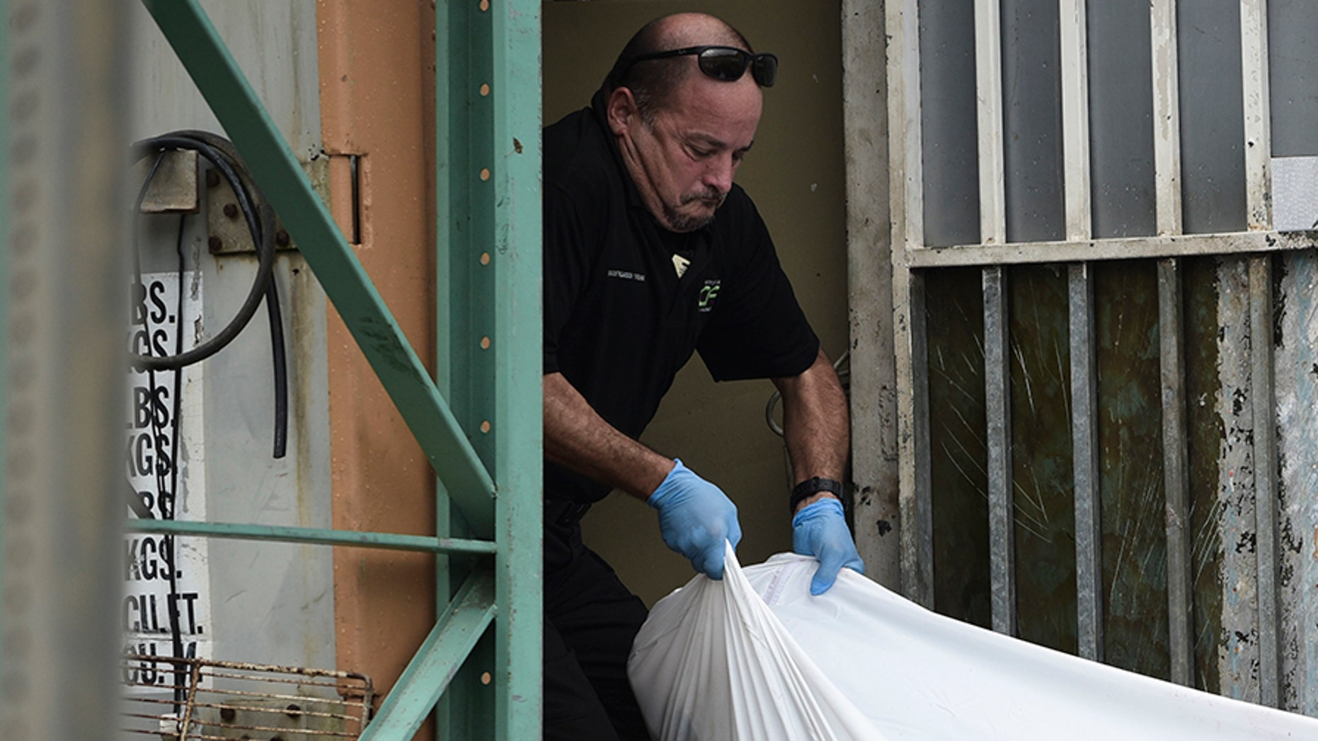 Forensic worker moves a body at a San Juan crime scene in January, Puerto Rico's deadliest month in recent years