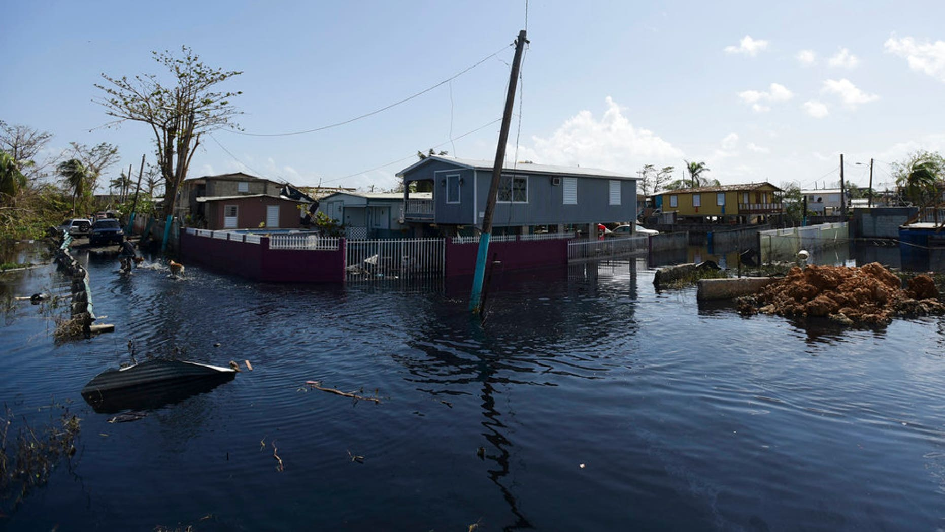 Homes in the Juana Matos community are surrounded by flood waters in Catano, Puerto Rico, Thursday, Sept. 28, 2017, one week after the passage of Hurricane Maria. The aftermath of the powerful storm has resulted in a near-total shutdown of the U.S. territory's economy that could last for weeks and has many people running seriously low on cash and worrying that it will become even harder to survive on this storm-ravaged island. (AP Photo/Carlos Giusti)