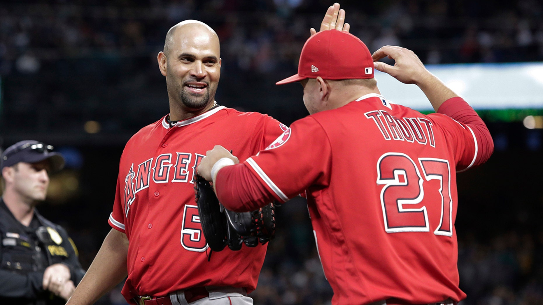 Los Angeles Angels' Albert Pujols celebrates with Mike Trout between the top and bottom of the fifth inning after Pujols singled for his 3,000th career hit, against the Seattle Mariners in a baseball game Friday, May 4, 2018, in Seattle. (AP Photo/Jason Redmond)