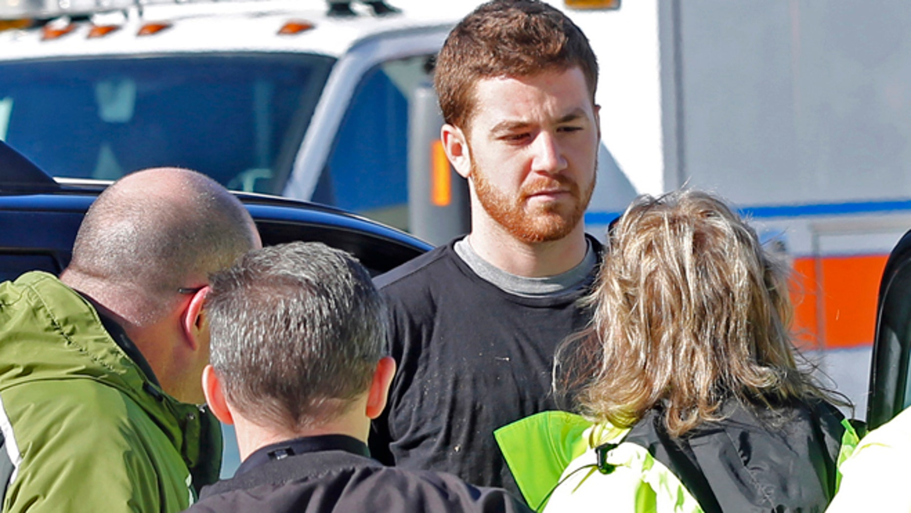EMS personnel speak with Cody Cousins, 23, who was detained after a shooting inside the Electrical Engineering building on the campus of Purdue University in West Lafayette, Ind.