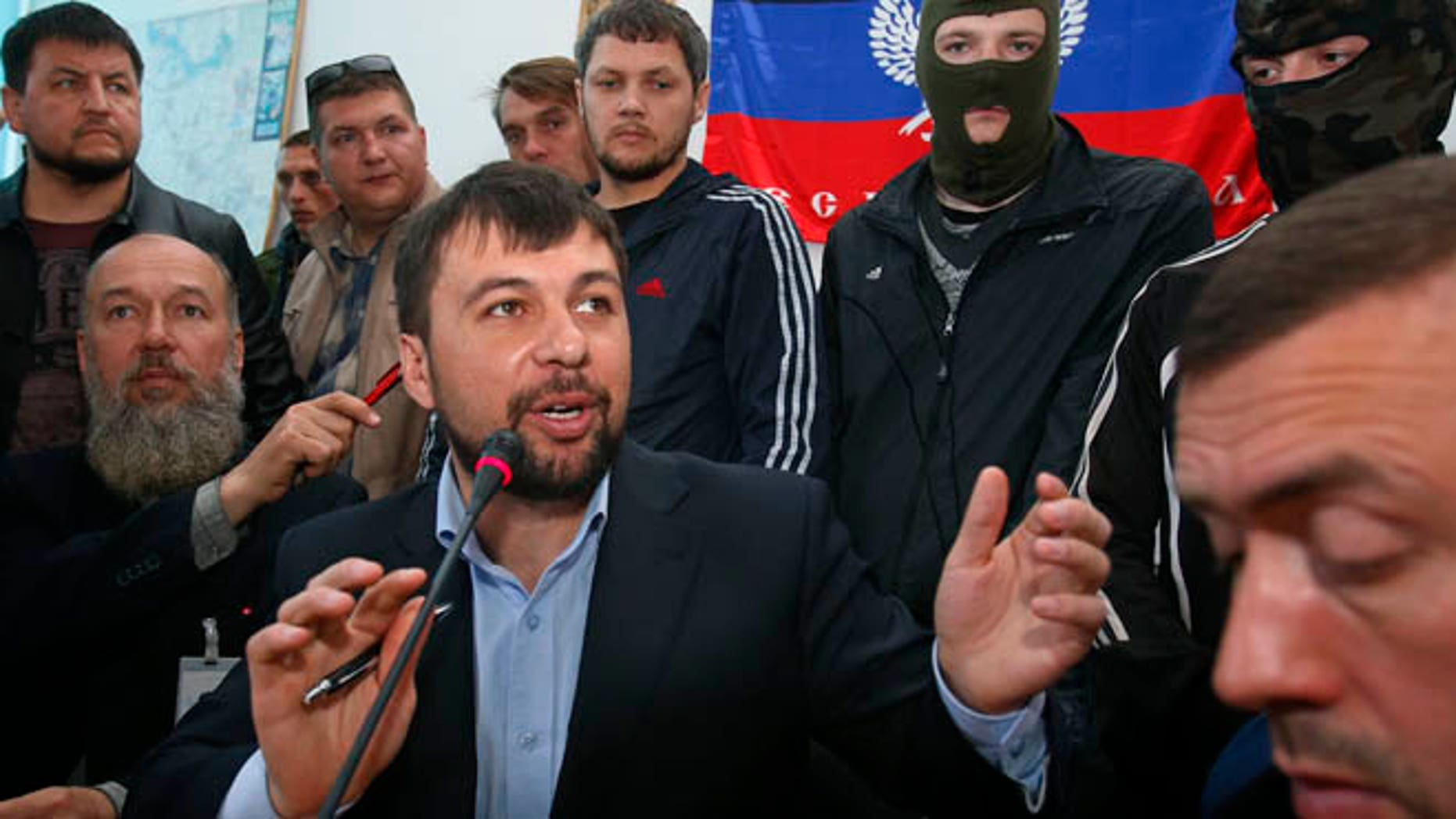 April 18, 2014: Denis Pushilin, foreground center,  spokesman of the self-appointed Donetsk Peoples Republic, speaks to reporters inside the regional administration building seized earlier in Donetsk, Ukraine.