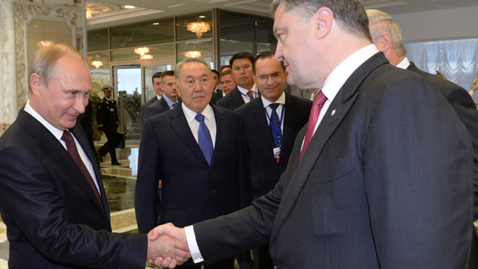 Aug. 26, 2014: Russian President Vladimir Putin, left, shakes hands with Ukrainian President Petro Poroshenko, right, as Kazakh President Nursultan Nazarbayev, center, looks at them, prior to their talks after after posing for a photo in Minsk, Belarus. Leaders of Russia, Belarus, two other former Soviet republics as well as top EU officials are meeting in Minsk, Belarus, for a highly anticipated summit to discuss the crisis in Ukraine which has left more than 2,000 dead and displaced over 300,000 people.