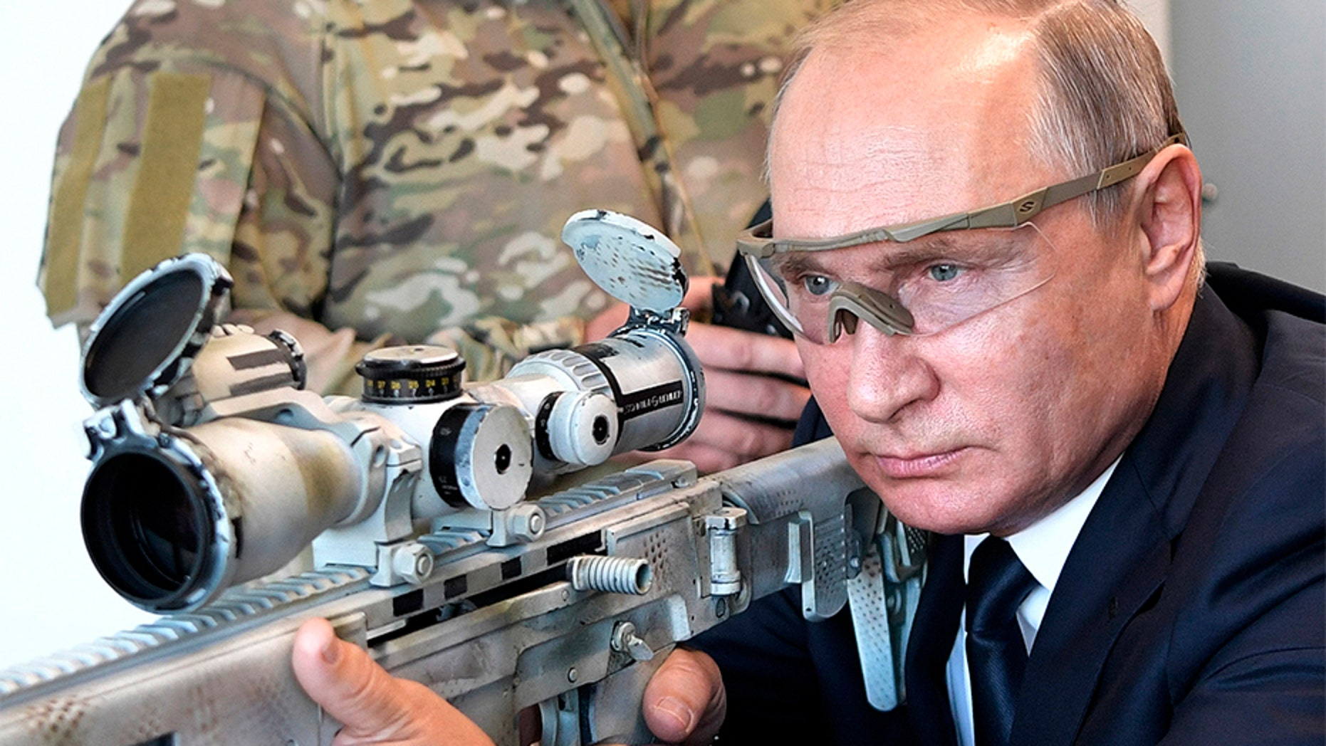 Russian President Vladimir Putin aims a sniper rifle during a visit to the Patriot military exhibition center outside Moscow, Russia.