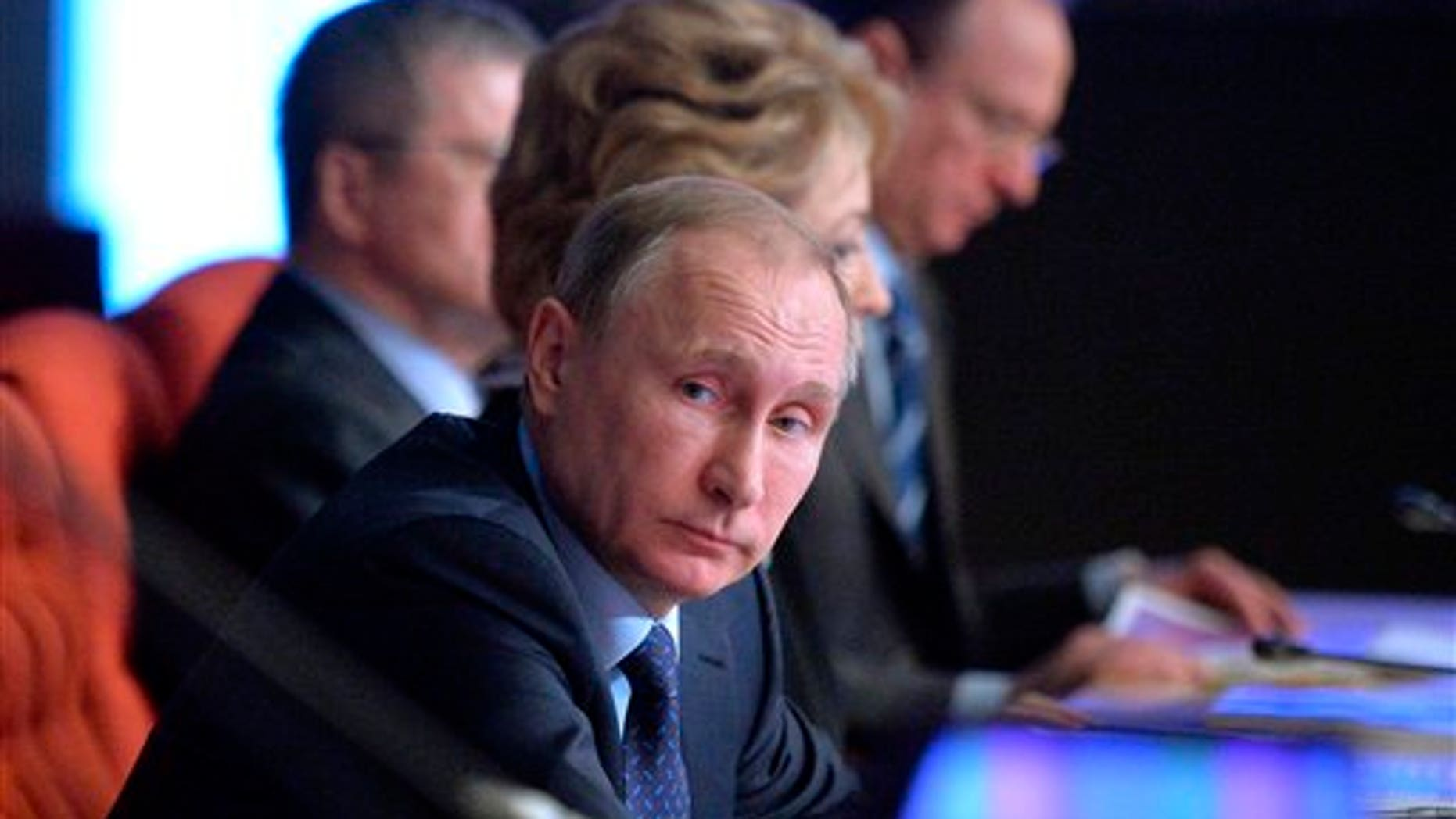 Russian President Vladimir Putin, foreground, listens during a meeting of Russian judges in Moscow, Russia, Tuesday, Feb.  16, 2016. (Alexei Druzhinin/Sputnik, Kremlin Pool Photo via AP)
