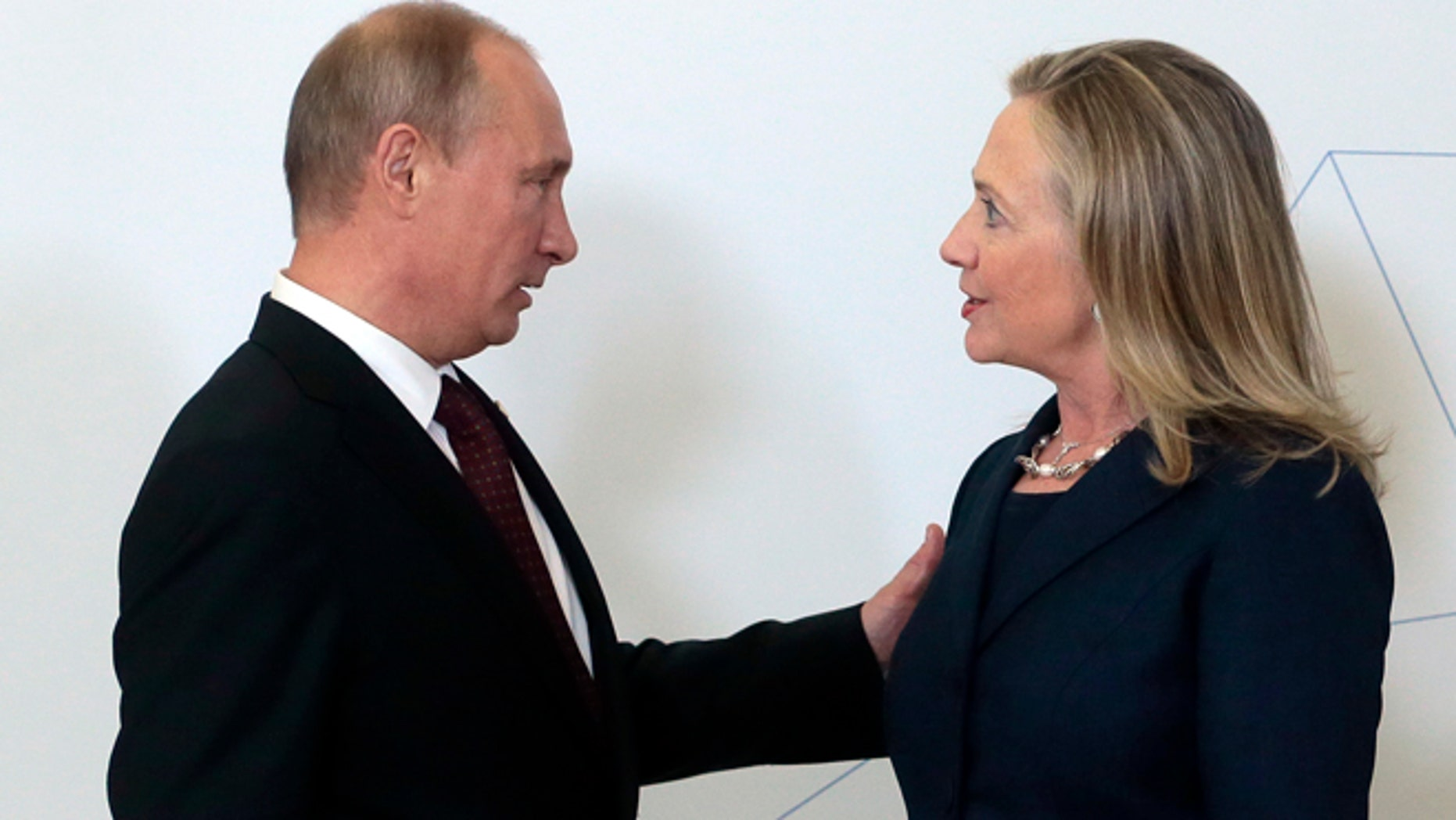 Sept. 8, 2012: Russian President Vladimir Putin, left, meets U.S. Secretary of State Hillary Rodham Clinton on her arrival at the APEC summit in Vladivostok, Russia.