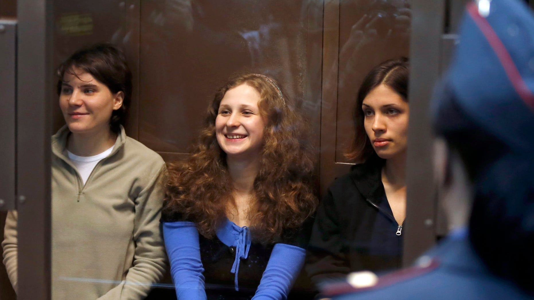 Oct. 10, 2012: Feminist punk group Pussy Riot members, from left, Maria Alekhina, Yekaterina Samutsevich and Nadezhda Tolokonnikova sit in a glass cage at a court room in Moscow.