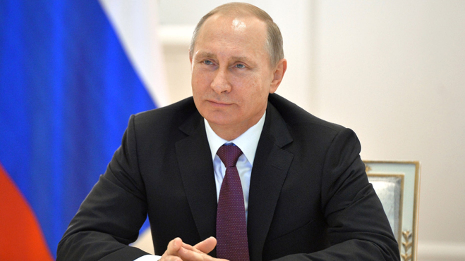 Russian President Vladimir Putin smiles during a live video link with members of Russian Geographical Society expedition to the Southern Pole in Moscow's Kremlin, Russia on Friday, Dec. 26, 2014.