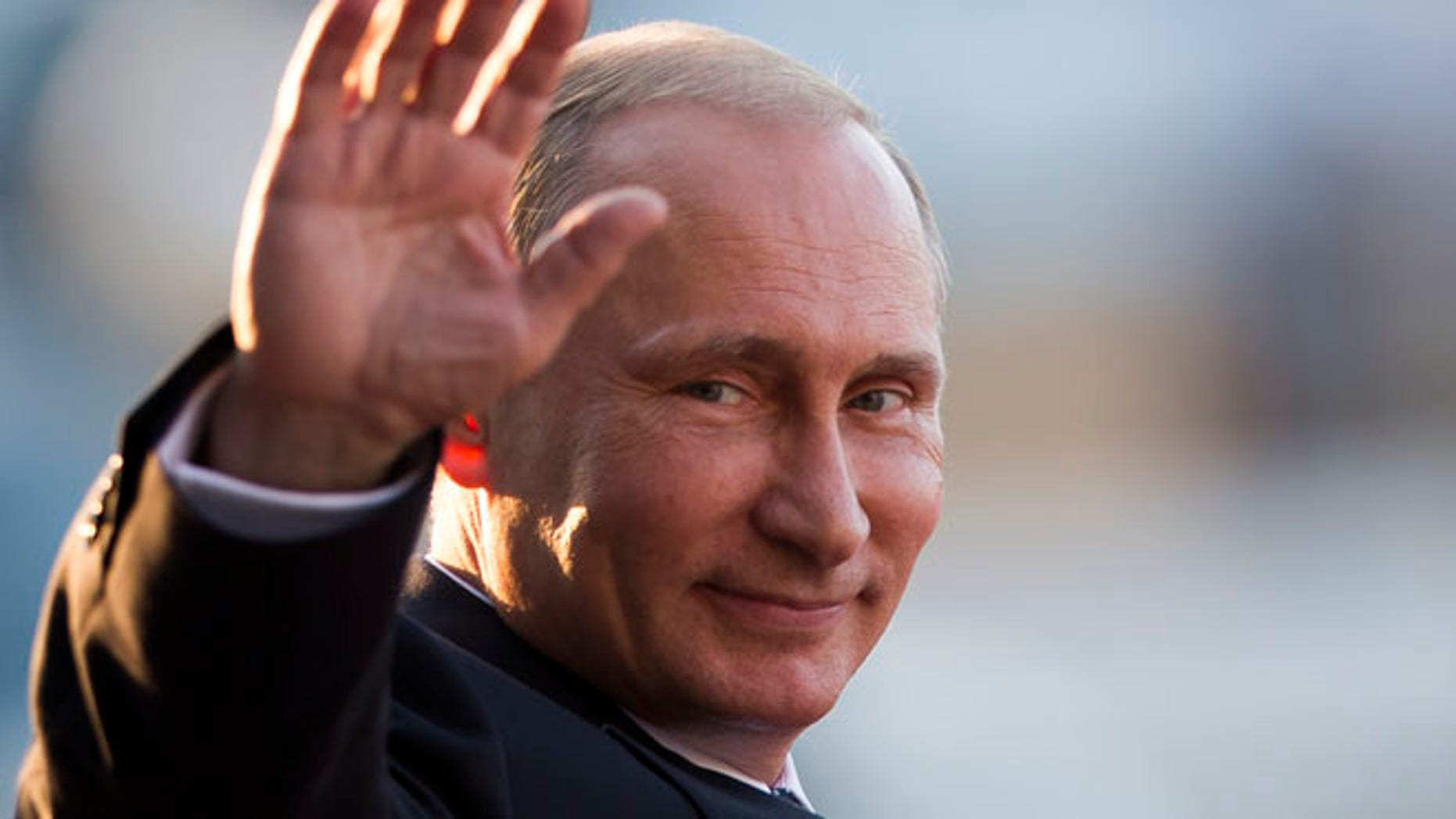 July 16, 2014: Russia's President Vladimir Putin waves to photographers as he leaves the Itamaraty Palace after attending the final day of the BRICS Summit in Brasilia, Brazil. (AP)