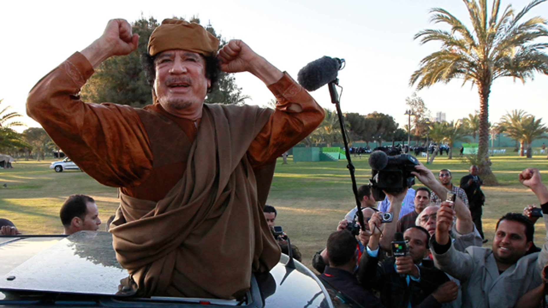 April 10, 2011: Libyan leader Moammar Qaddafi waves at his supporters people in Tripoli