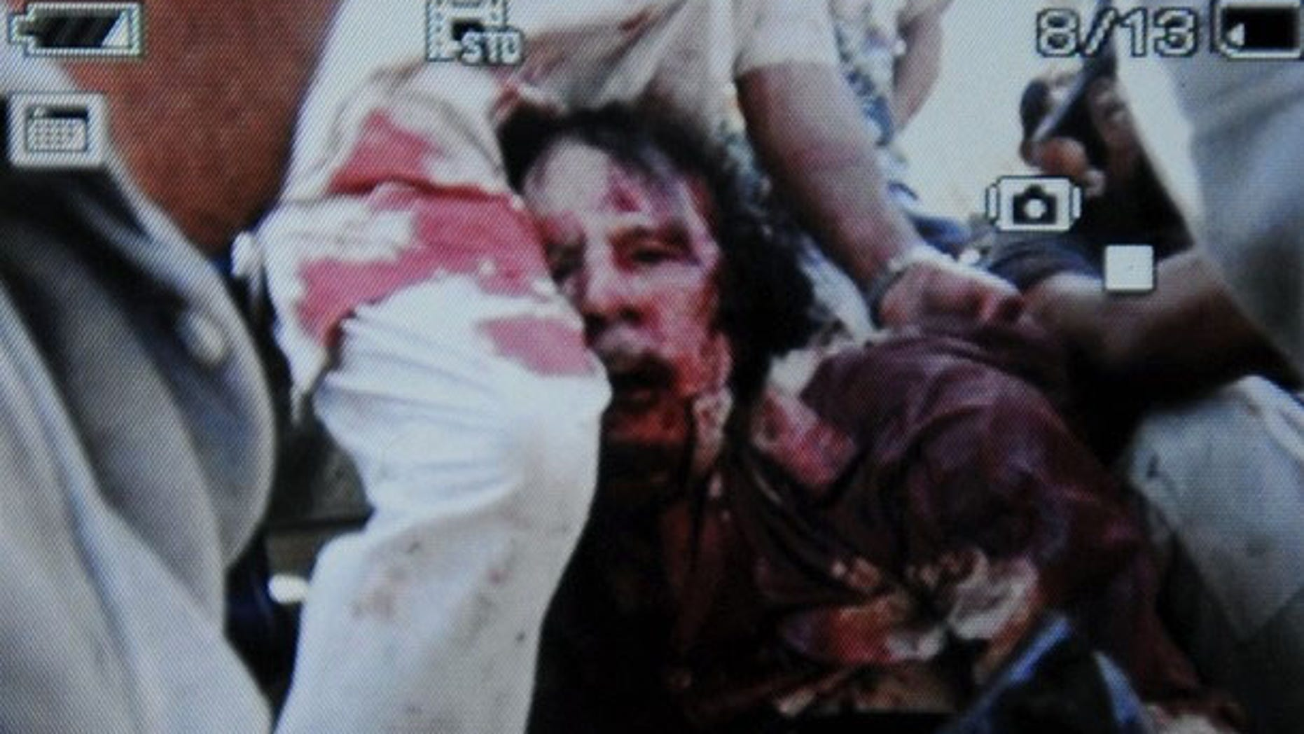 An image captured by AFP from a cell phone purportedly shows a wounded or dead Muammar Qaddafi.