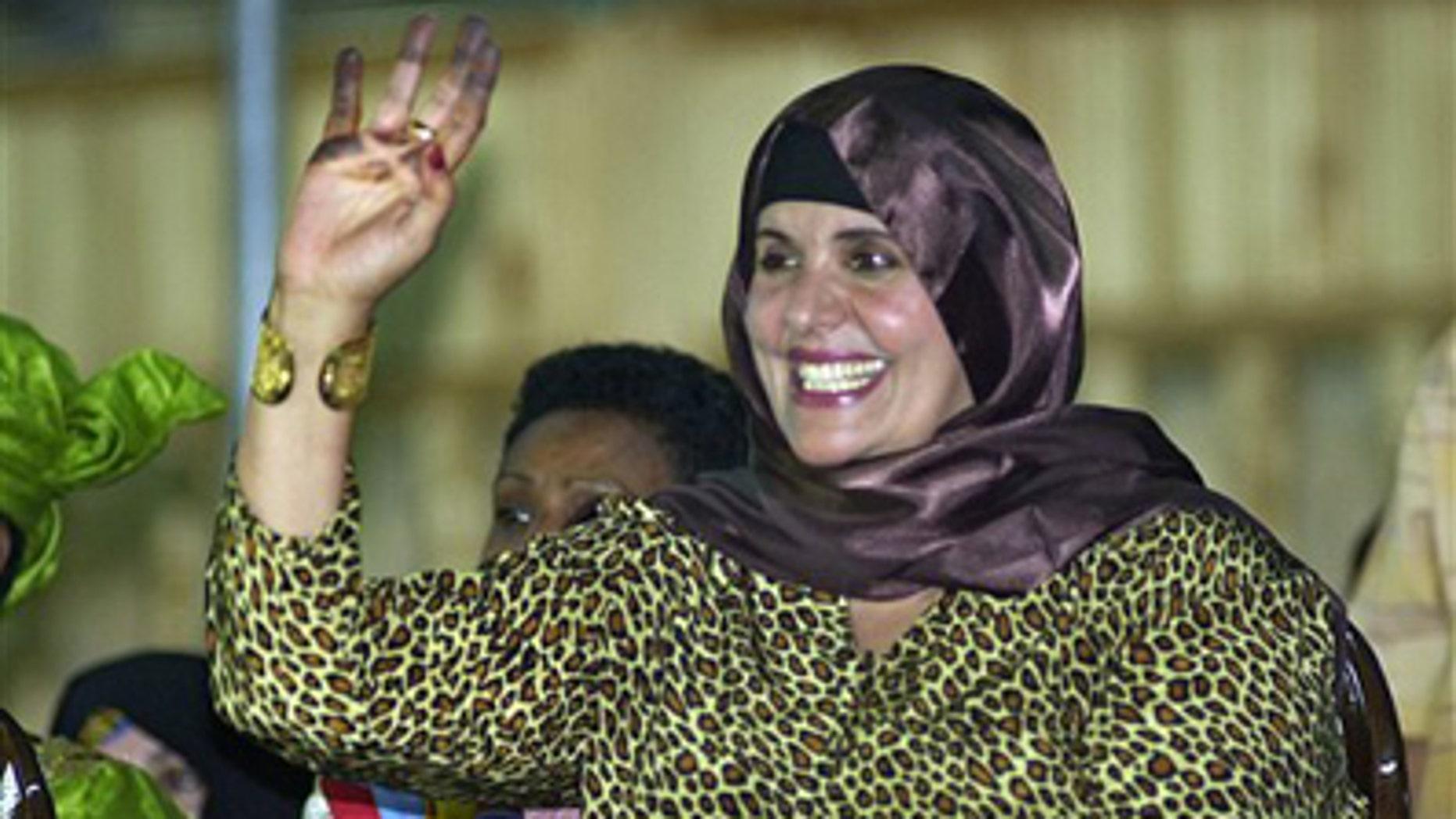 In this Monday, Sept. 1, 2003 file photo, showing Safiya Gadhafi, the wife of Libyan leader Muammar Qaddafi, waves at Libyan soldiers during a military parade at Tripoli's main square.