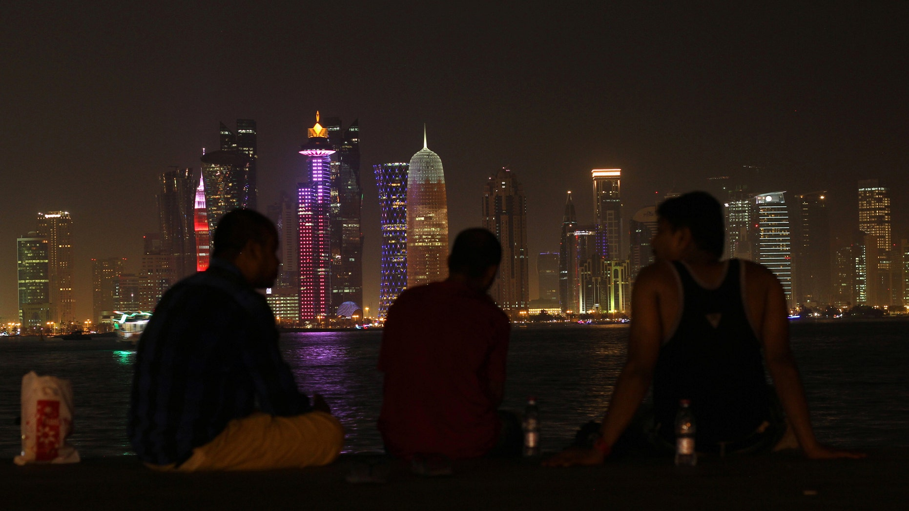 People sit on the corniche in Doha, Qatar, June 15, 2017.