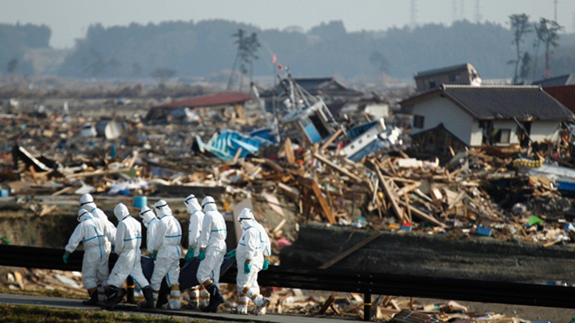 April 15: Japanese police officers carry a body during search and recovery operation for missing victims in the area devastated by the March 11 earthquake and tsunami in Namie, Fukushima Prefecture, northeastern Japan. In the background is part of the Fukushima Dai-ichi nuclear complex. (AP)