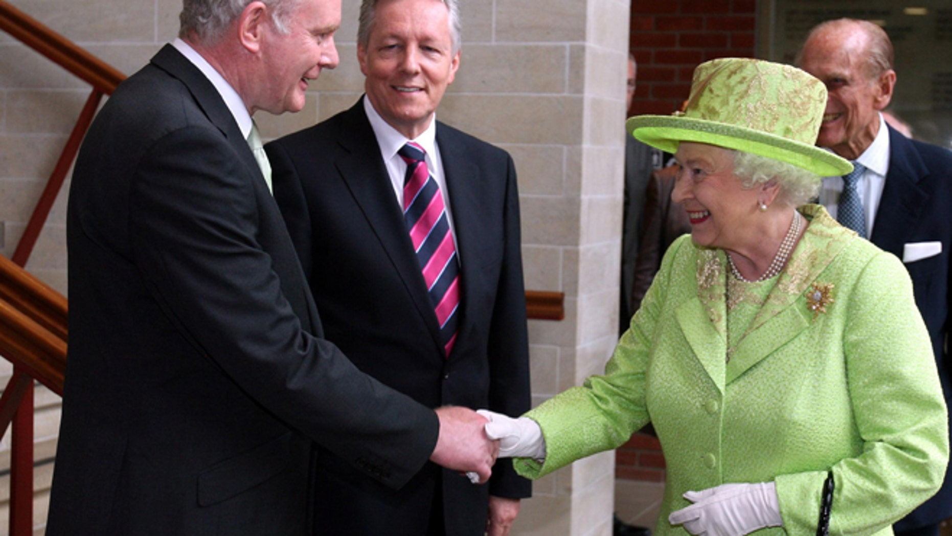 June 27, 2012: Britain's Queen Elizabeth II shakes hands with Northern Ireland Deputy First Minister and former IRA commander Martin McGuinness watched by First minister Peter Robinson, centre, at the Lyric Theatre in Belfast, Northern Ireland.
