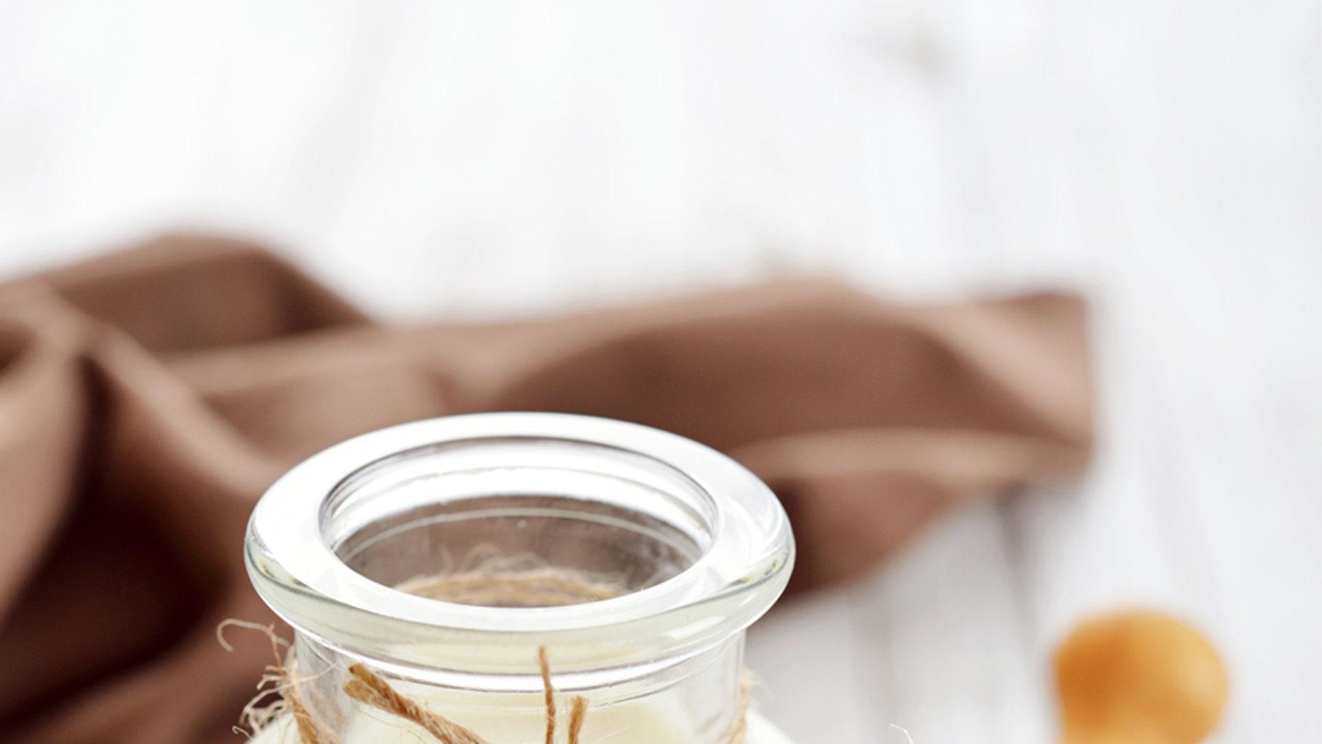 Quinoa milk in glass bottle on wooden background