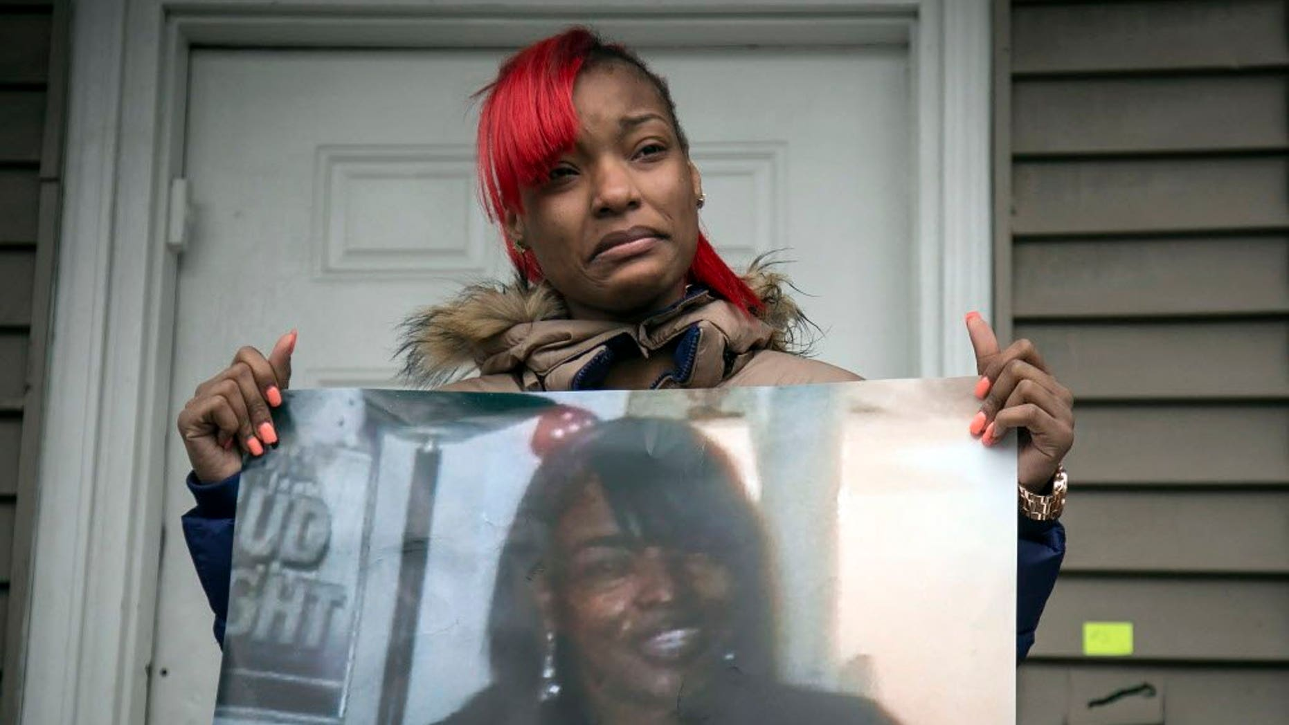 Latonya Jones holds a photo of her mother, Bettie, during a vigil in December. Bettie Jones and Quintonio LeGrier, were killed by Chicago police in December.