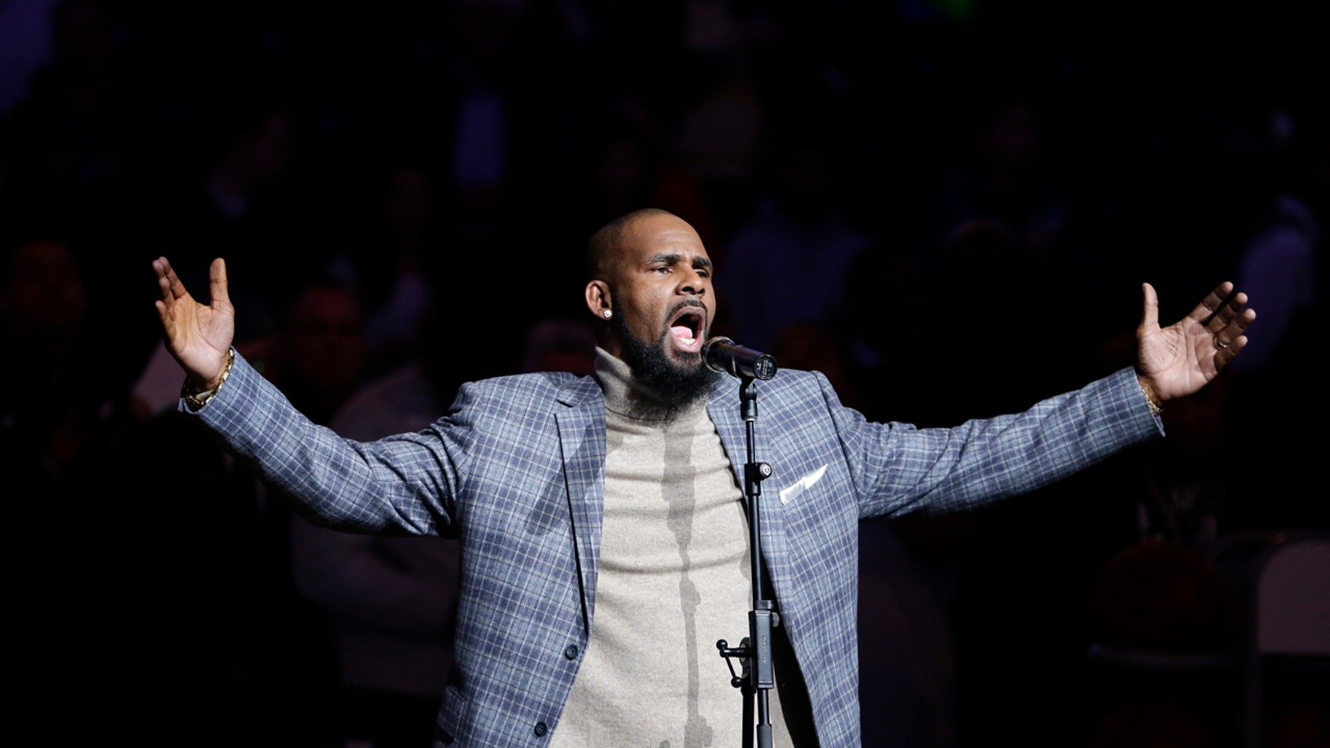 FILE - In this Nov. 17, 2015 file photo,  R. Kelly performs the national anthem before an NBA basketball game between the Brooklyn Nets and the Atlanta Hawks in New York. Court documents show the R&B singer  has been evicted from two Atlanta-area homes over unpaid rent.  The Feb. 13, 2018 filings with the Fulton County magistrate court show Kelly owes more than $31,000 in past due payments to SB Property Management Global.  (AP Photo/Frank Franklin II, File)