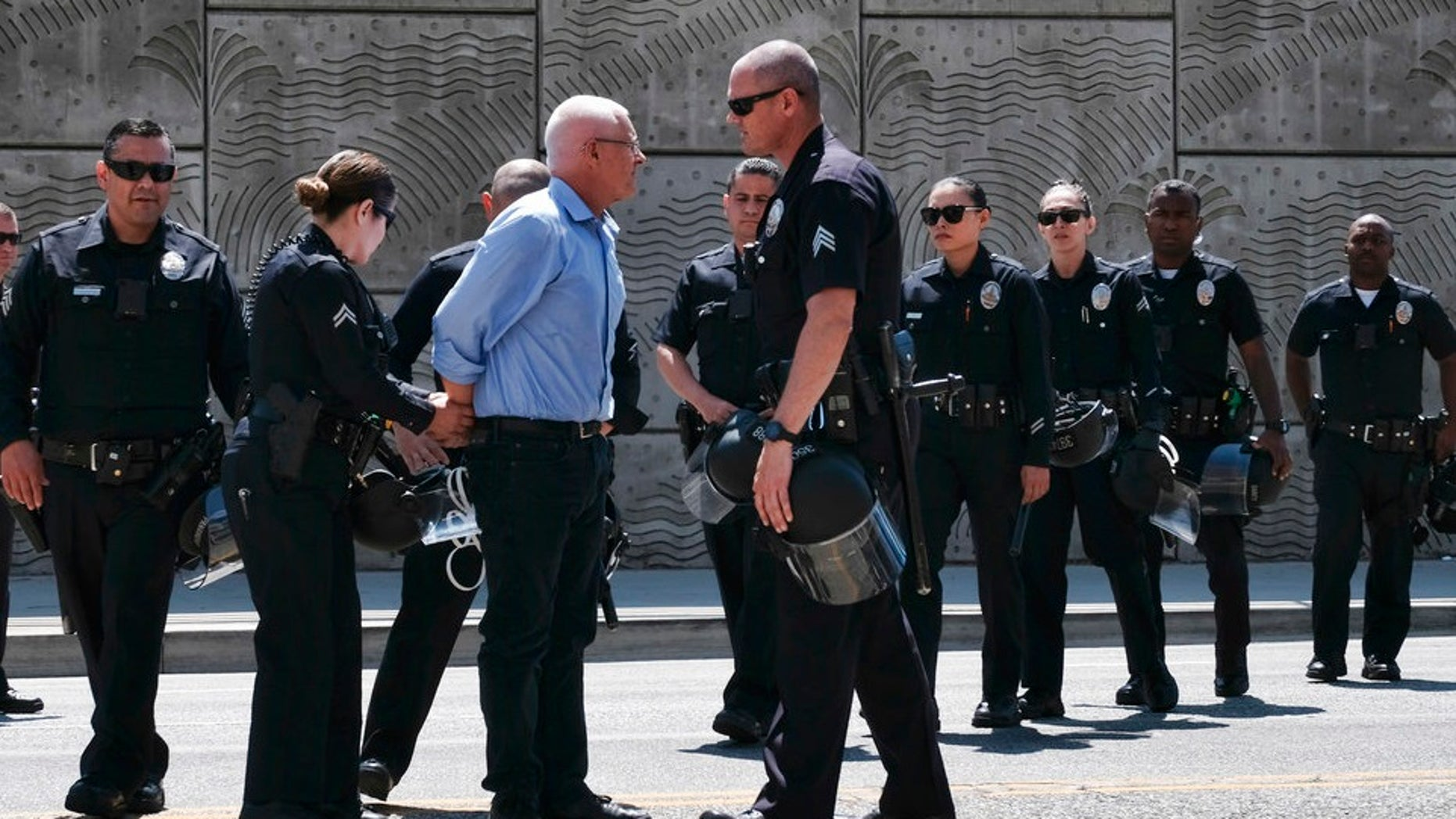 LA City Councilman Mike Bonin is handcuffed after being arrested for blocking entrance to a downtown ICE facility.